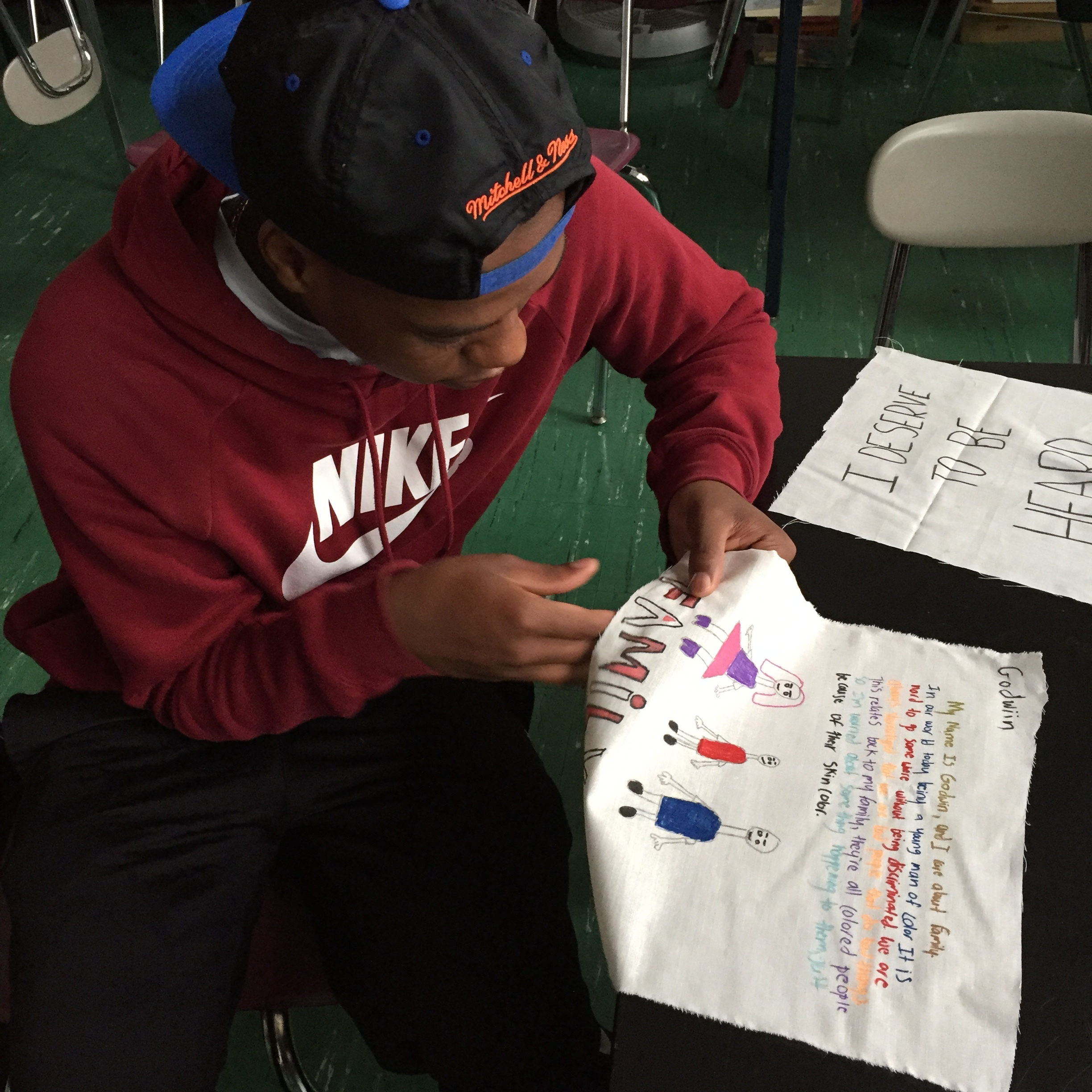 A student finishing his quilt piece drawing on bullying.