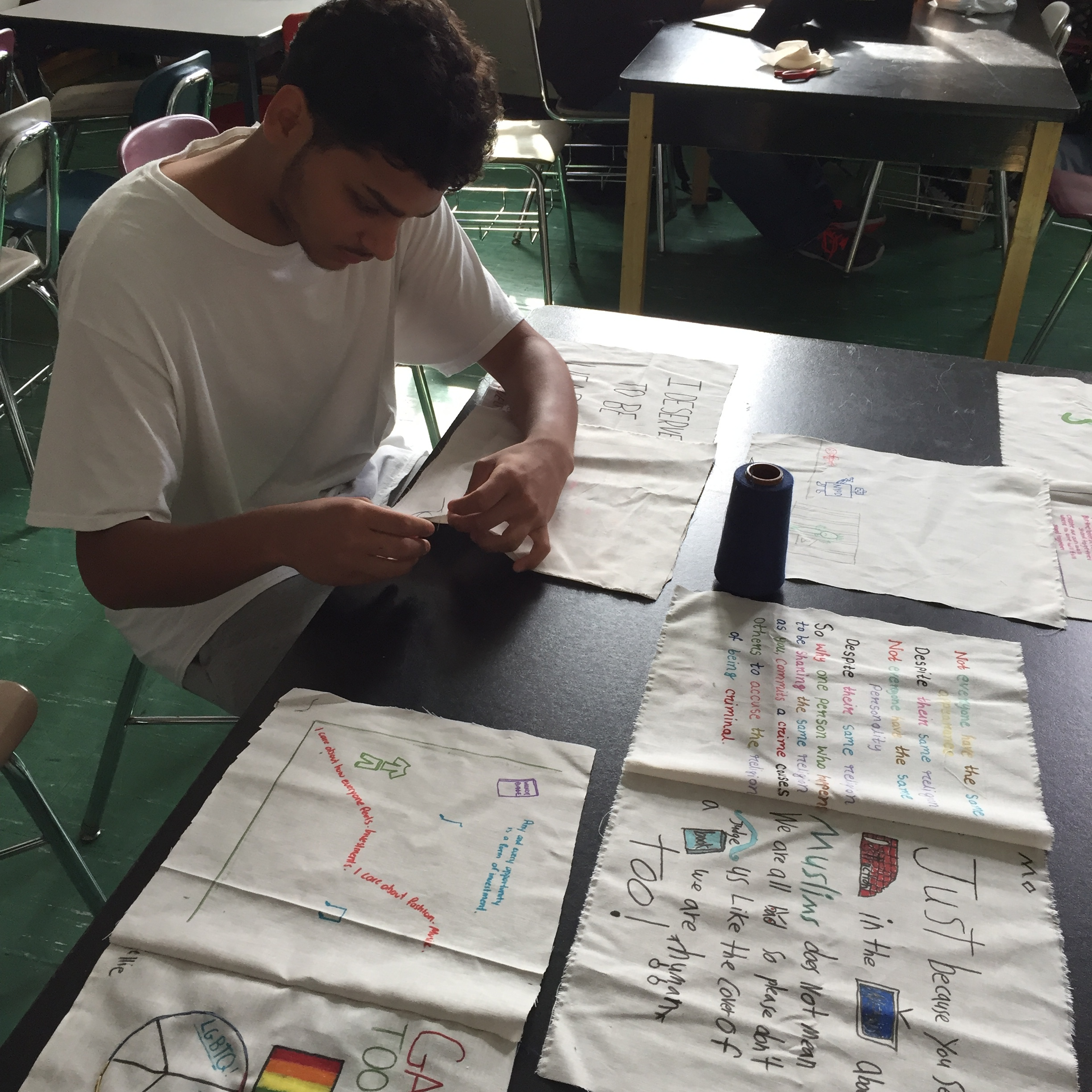 A student hand stitching the quilt pieces together.