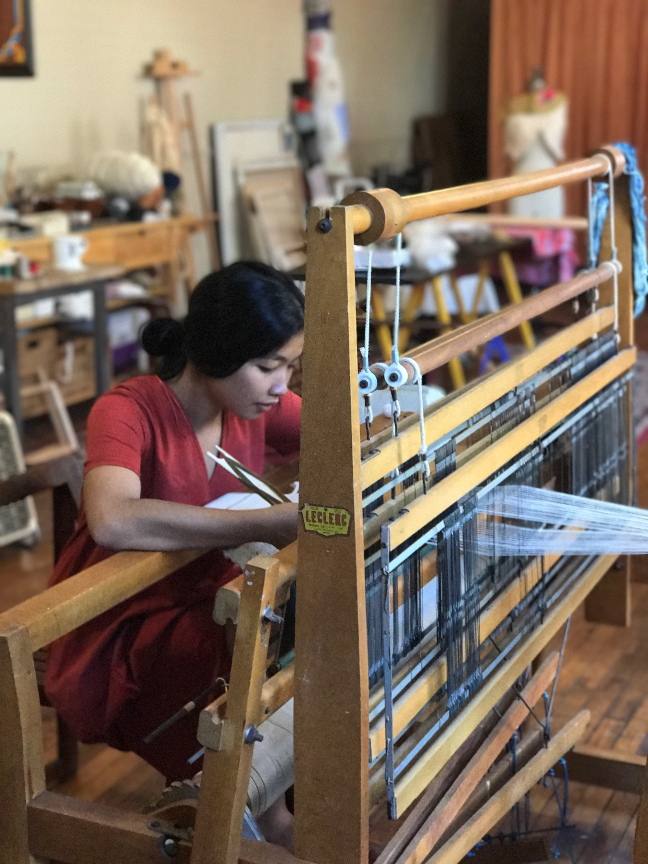 A photo of me weaving on my favorite floor loom in my studio. In the background are yarn, canvases, an easel, a fashion form, drafting table, and shelving for my supplies.