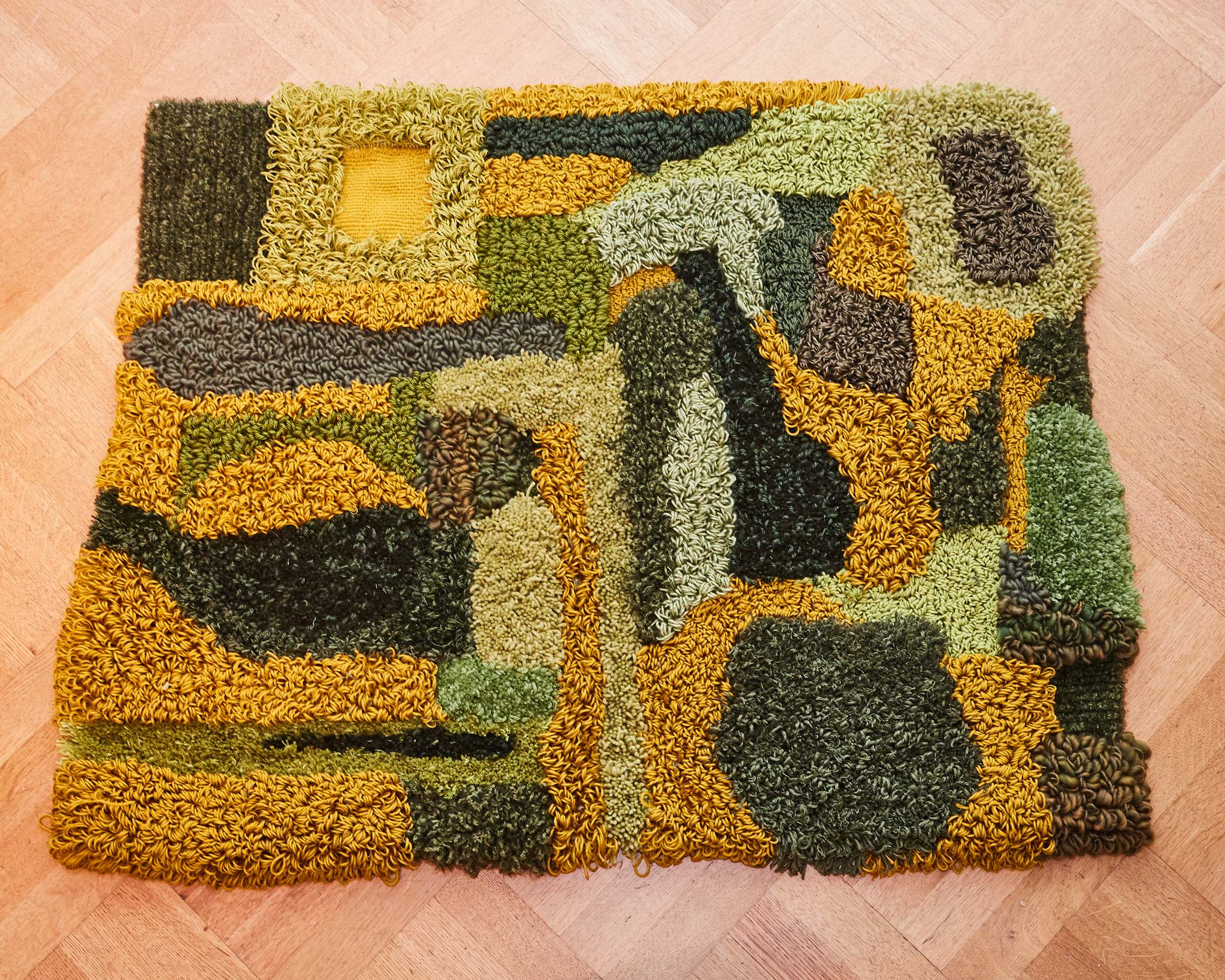 The rug on the floor. The colors are intensified due to the high light exposure. There are many different texture made from different types of yarns, tufting heights, and loop structures.