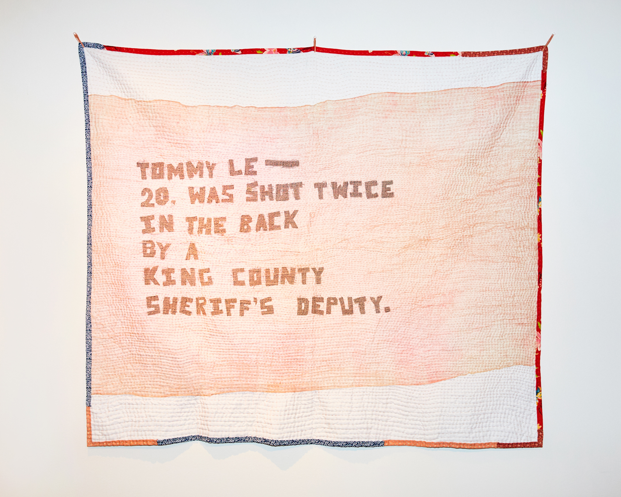 """The front of the quilt consists of hand-cut letters in black on top a white background to read """"Tommy Le—20, was shot twice in the back by a King County Sheriff's Deputy."""" An earth tone (pinkish) gauzy fabric is draped on top of the letters. The entire quilt is hand-stitched with horizontal lines. The lines are spaced out at .25 inch."""