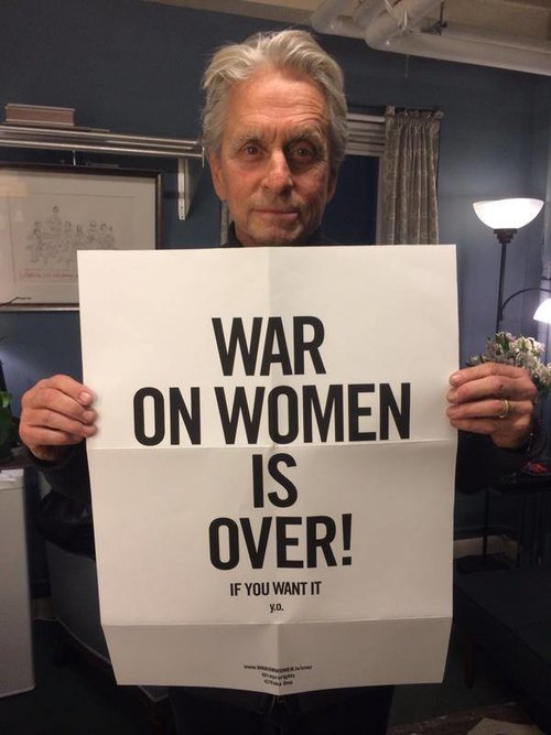 "Actor Michael Douglas holding the ""War on Women is Over! If You Want It"" poster"