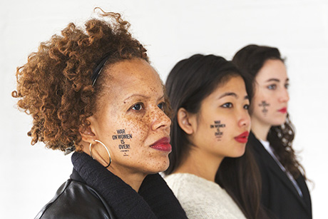 "Three women from different racial backgrounds looking forward with ""War on Women is Over! If You Want It"" temporary tattoos on their cheeks."