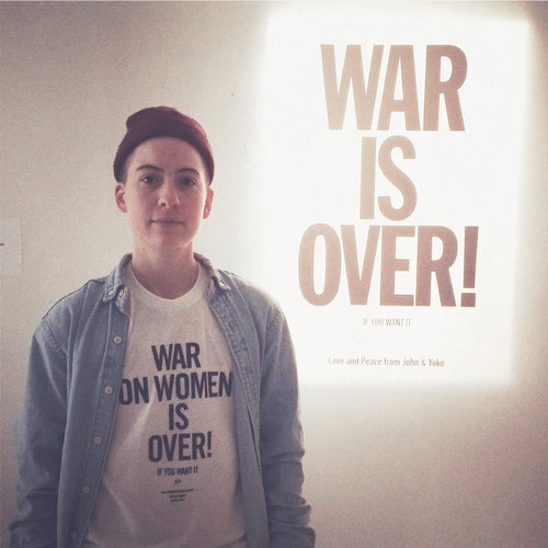 "Rae Tutera, LGBTQ clothier and activist, wearing the T-shirt in front of Yoko Ono's ""War is Over!"" projection at MoMA PS1"