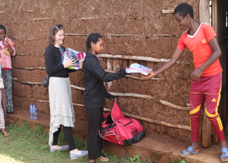 Saruma school boys pick up their hygiene packages from Cindy and her daughter.