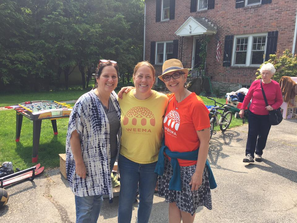 Left to right: Board member Denise Faneuff, Executive Director Liz McGovern, and Board member Gina DaCruz soak up the sunshine at the 7th annual WEEMA Yard Sale