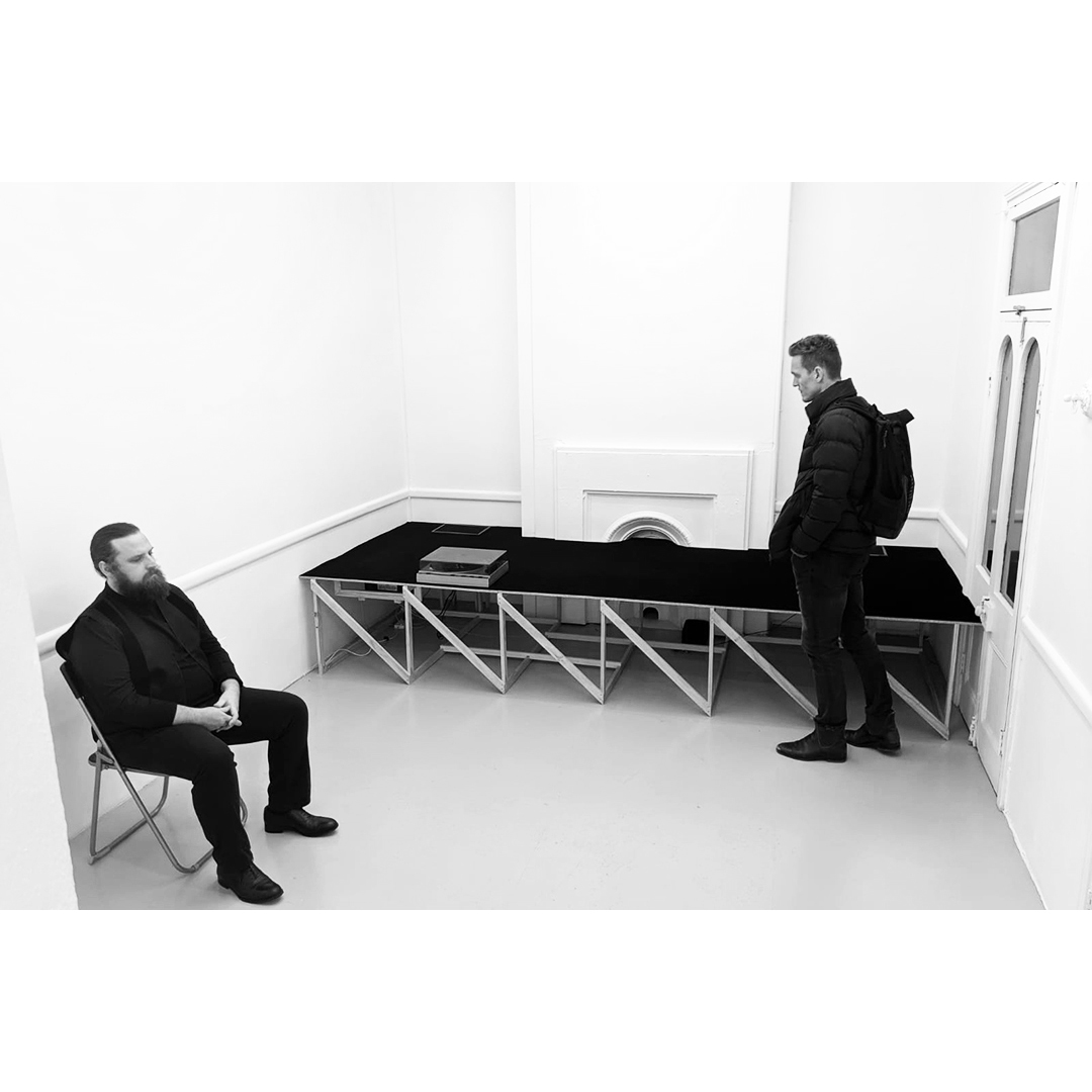 Installation View: COMA gallery, opening night,  This Is Not A Love Song  Aug 2nd, 2019. Pictured, Invigilator Jack Prest (left);  This Is Not A Love Song Installation,  2019, 14:52mins, Vinyl, Record Player, Timber, Chroma-key Black Velvet, 60 x 120 x 360cm (Centre); Gallery visitor (Right).