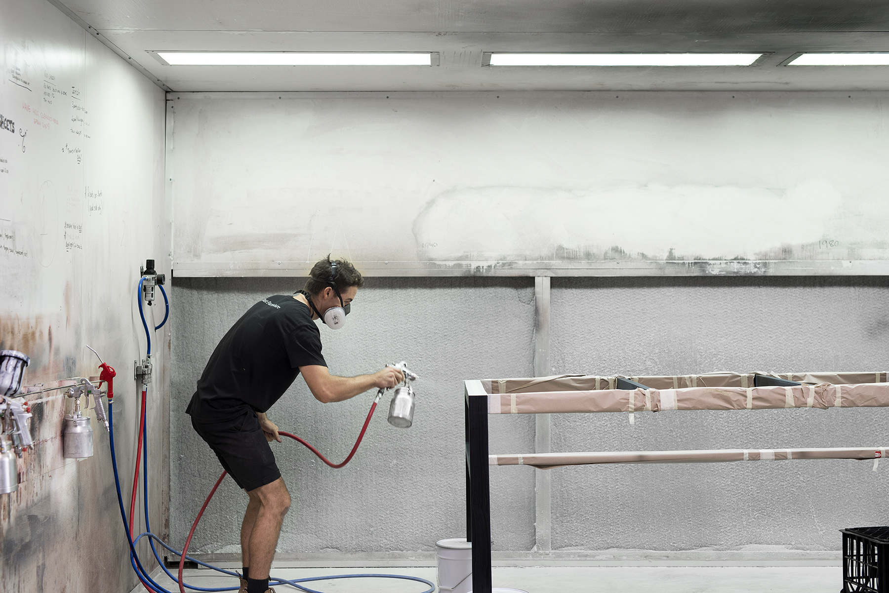The spraybooth is located in the middle of the workshop. Rory spays a coat of colour onto a Willox table frame to stain the wood. The table will then need to be sanded and another coat of colour applied.