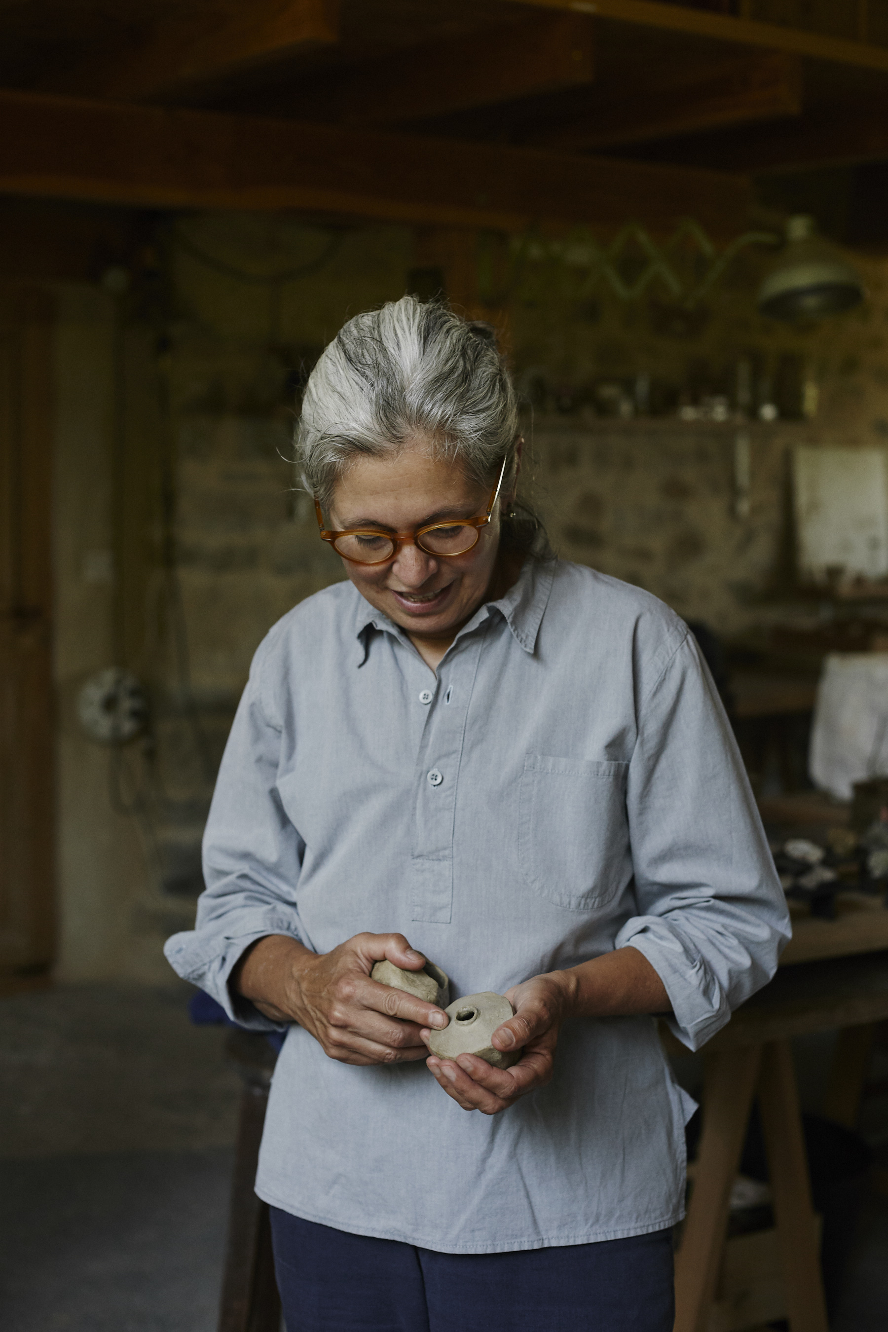 Artist Cécile Daladier holding a piece made from clay from her property in rural France.