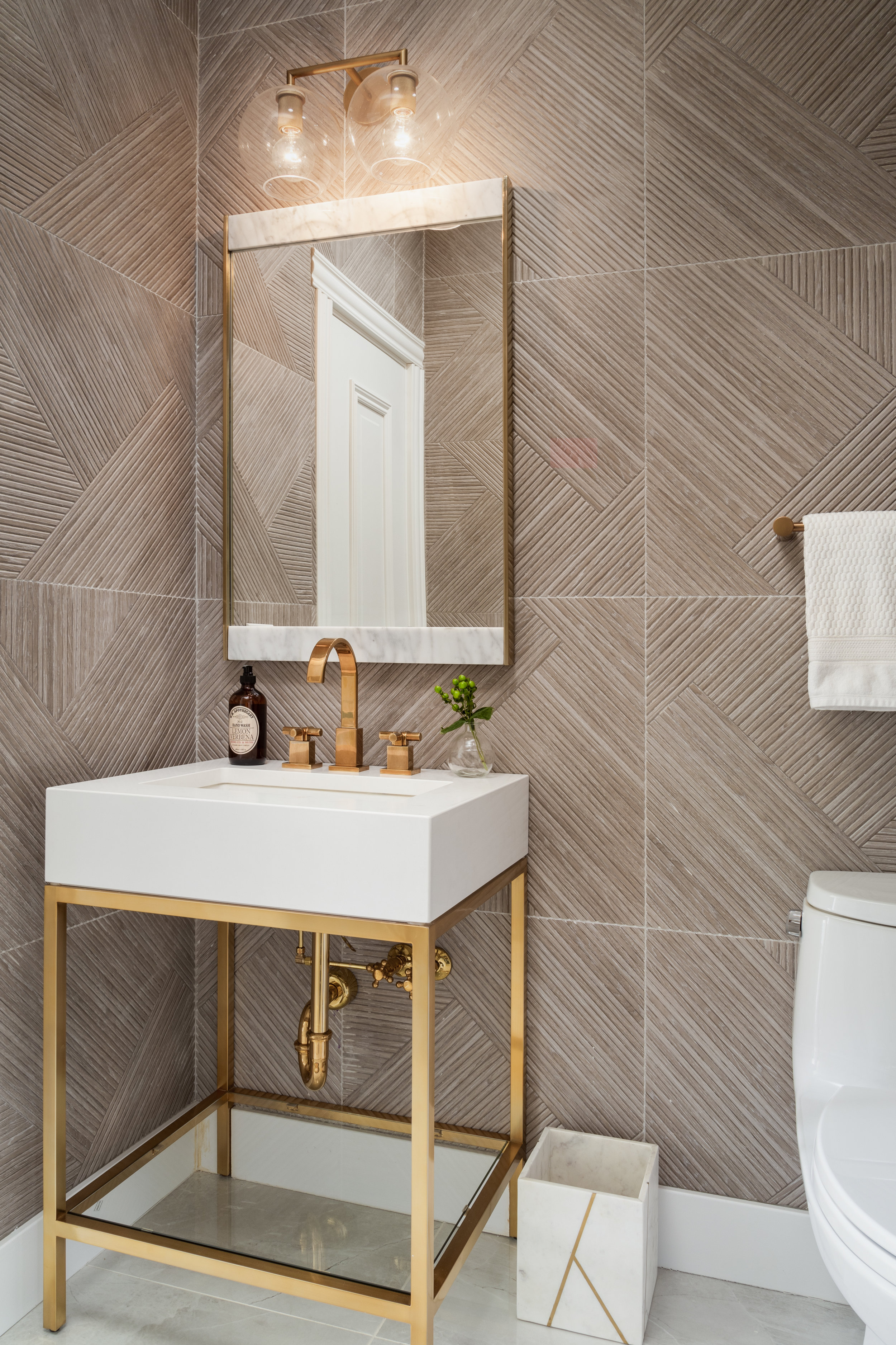 The Powder Room needed to be special. We tiled all four walls with a textural wood-looking tile that carried in the same colors and tones from the kitchen backsplash but in a more random pattern. A brass and white pedestal sink acts as jewelry in the room and is a more delicate balance from the heavy texture on the walls.