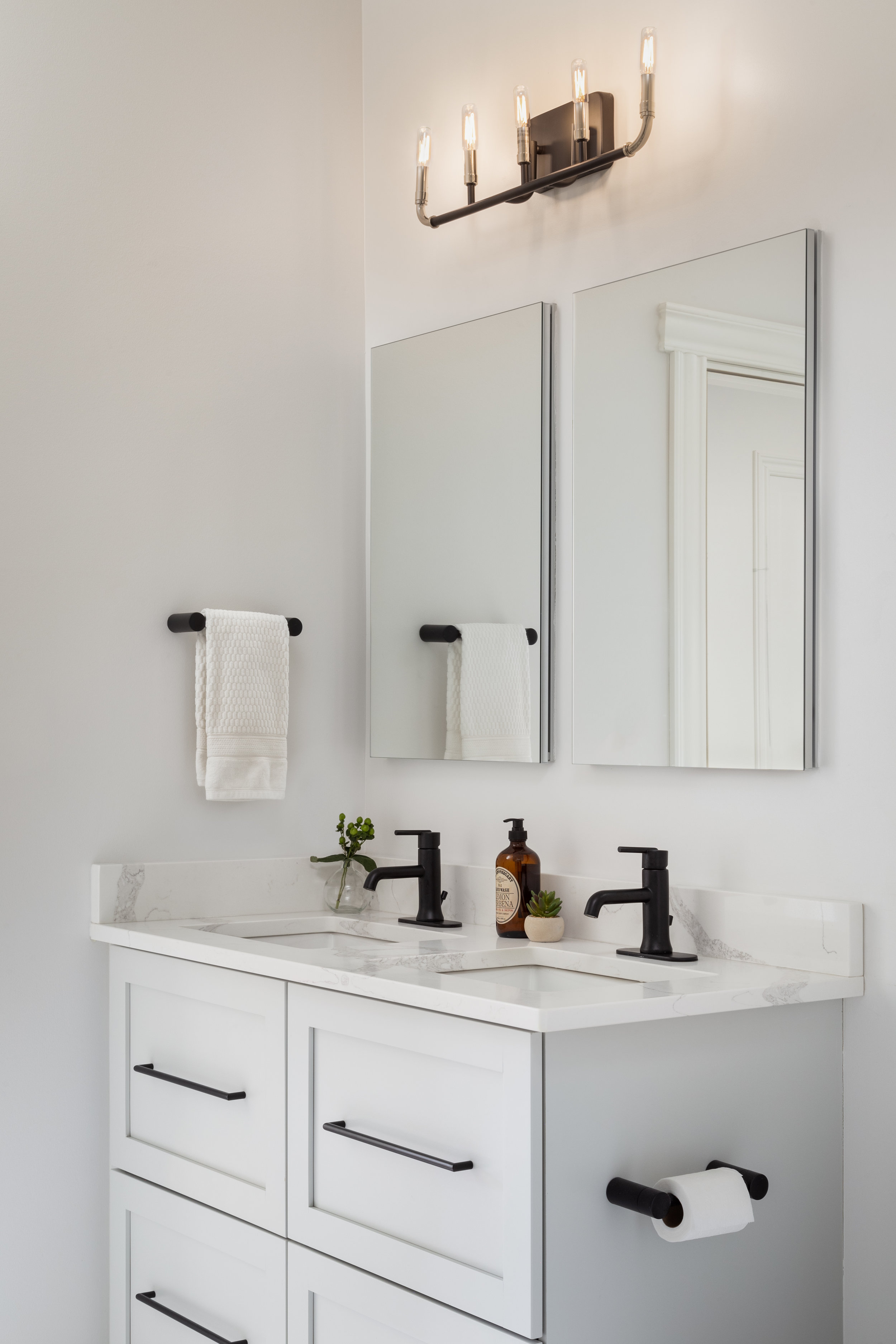 We kept the palette fresh and bright in the Jack and Jill bathroom that the two boys share. Black metal accents contrast the lighter finishes to add contrast and make it a little more masculine. We kept the cabinet profiles consistent with the kitchen cabinets to create a cohesive feel throughout the house.