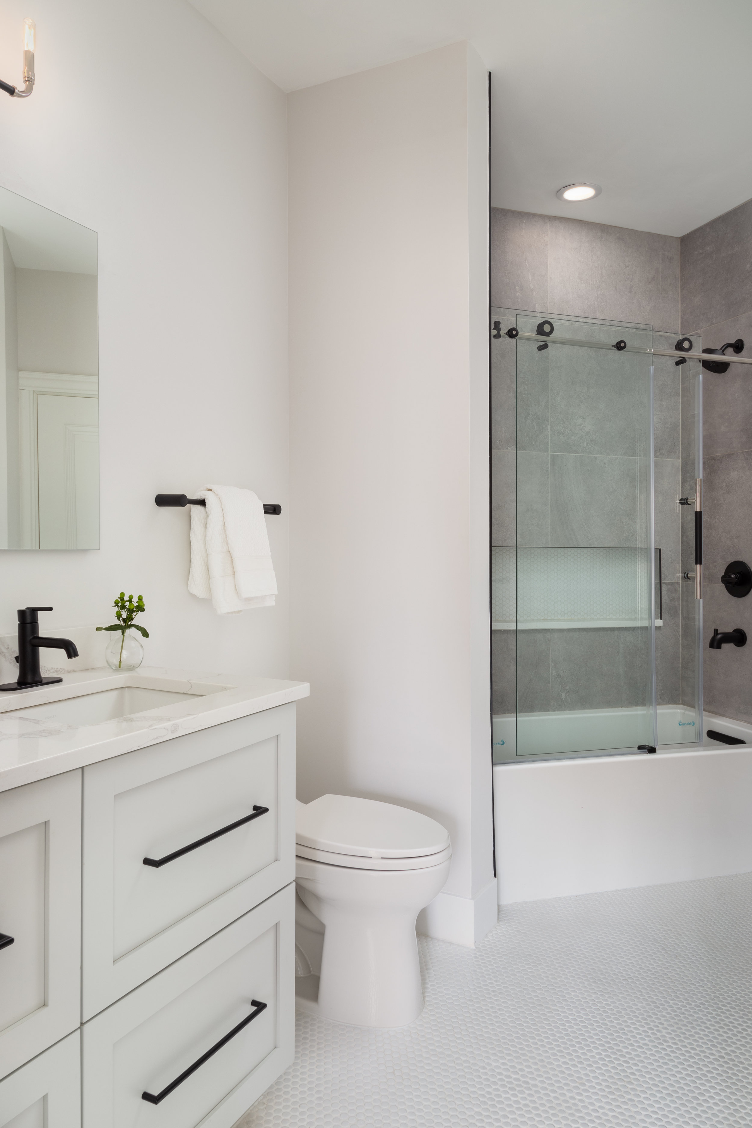 Clean, white penny tiles on the floor create a subtle texture and keep the kids from slipping on a wet floor. In the shower, we tiled the walls with a concrete-looking porcelain tile to add some natural texture and depth.