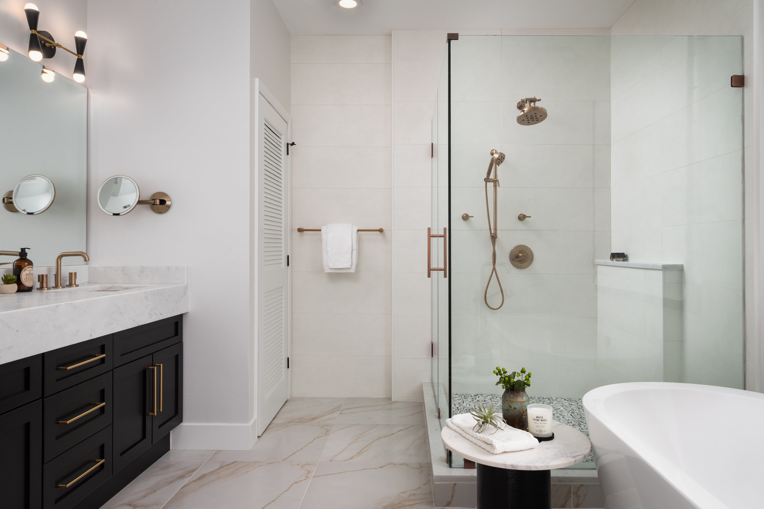 The Master Bathroom had to be the most special one in the house. We carried in a marble looking porcelain tile floor with a complementing wall tile that resembles a creamy Venetian plaster. The corner shower has a textured tile on the floor and a ledge built out on the side for toiletries.  Brizo  plumbing fixtures add a luxurious touch to the room.