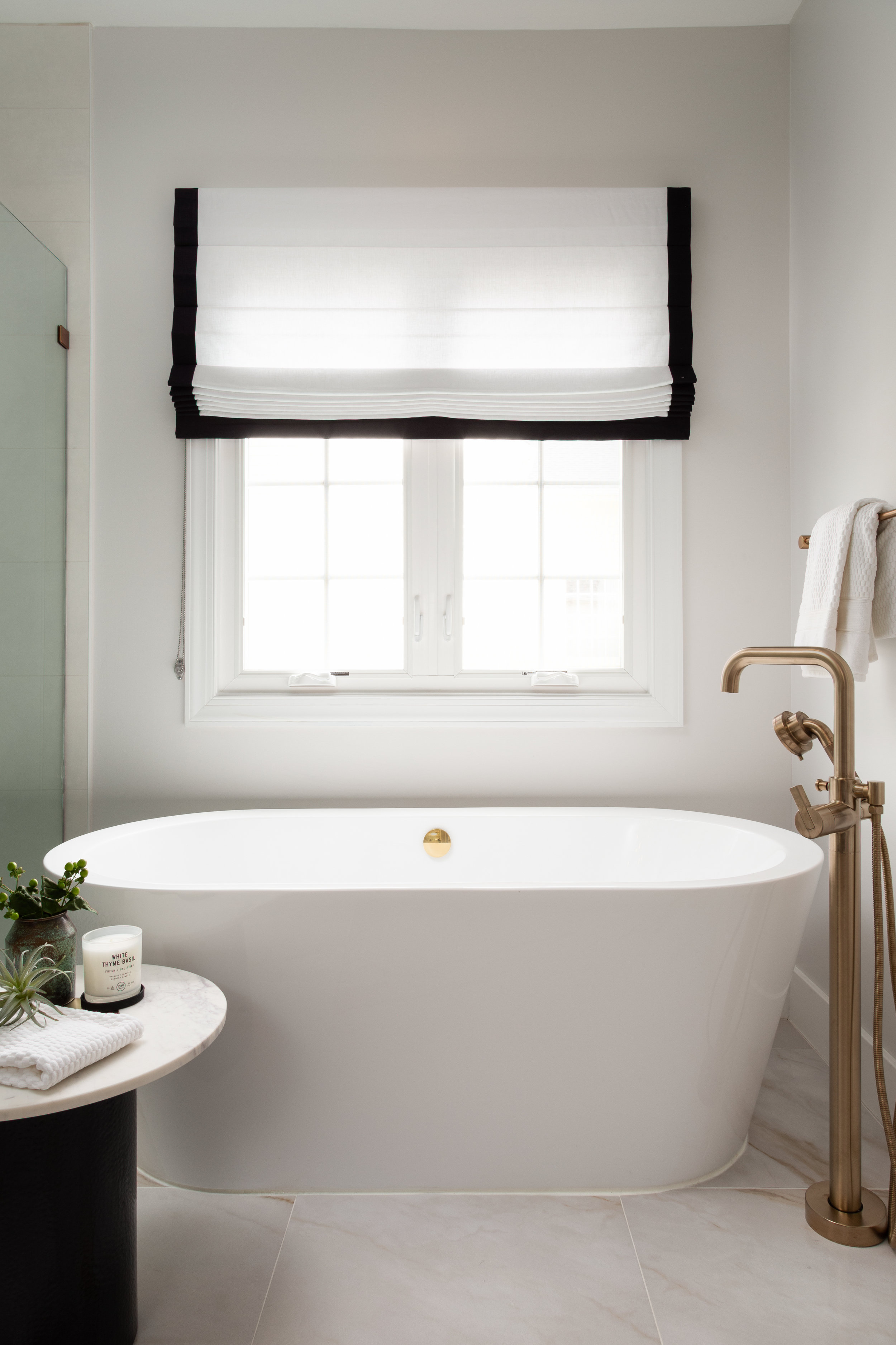 This room wouldn't be complete without a free-standing soaking tub beneath it's window. We added some linen roman shades for privacy with a black border to tie in with the vanity.