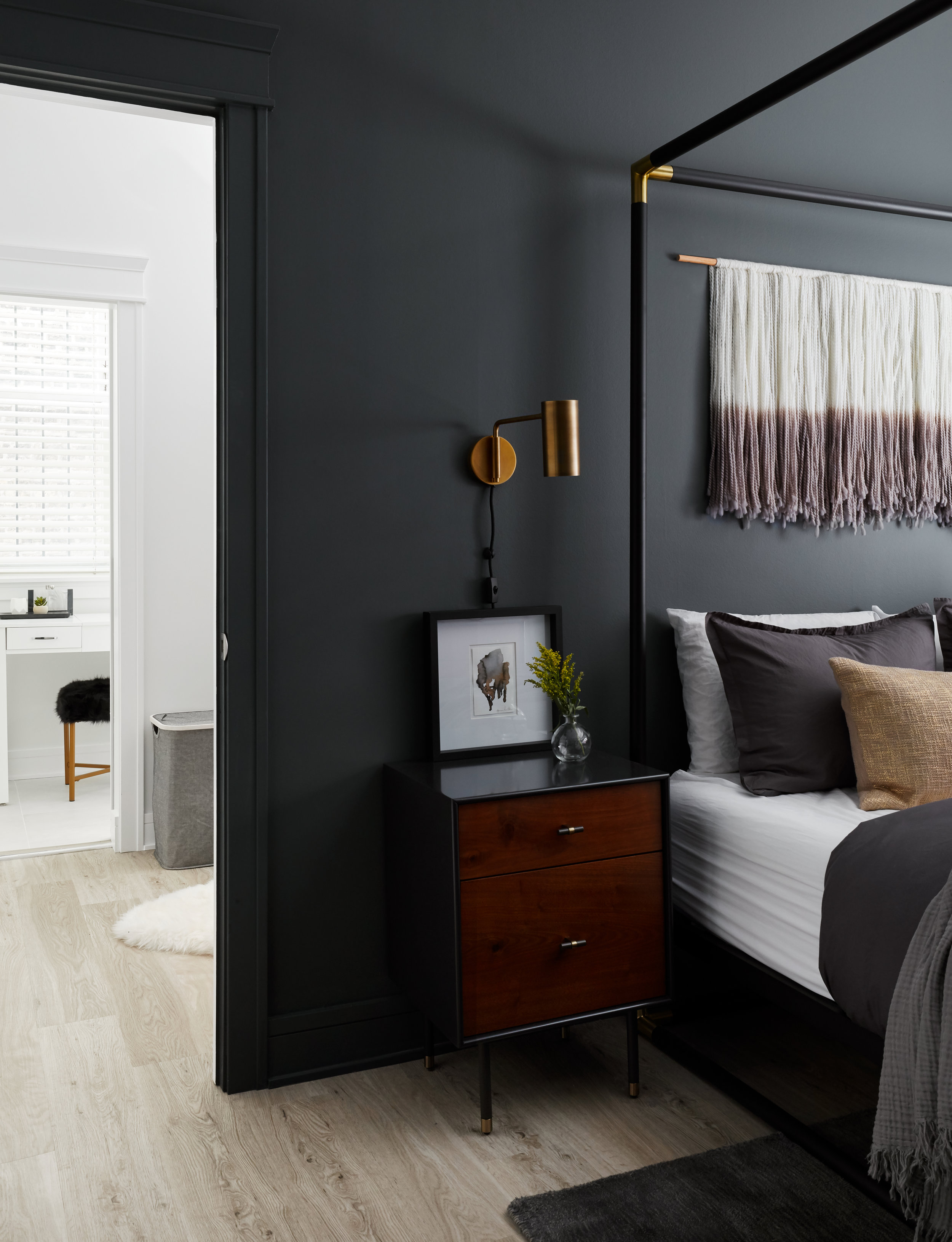 We carried the new, lighter floors into the master suite to contrast the moody, dark bedroom. The bedroom opens up to the new walk-in closet and en-suite master bathroom.