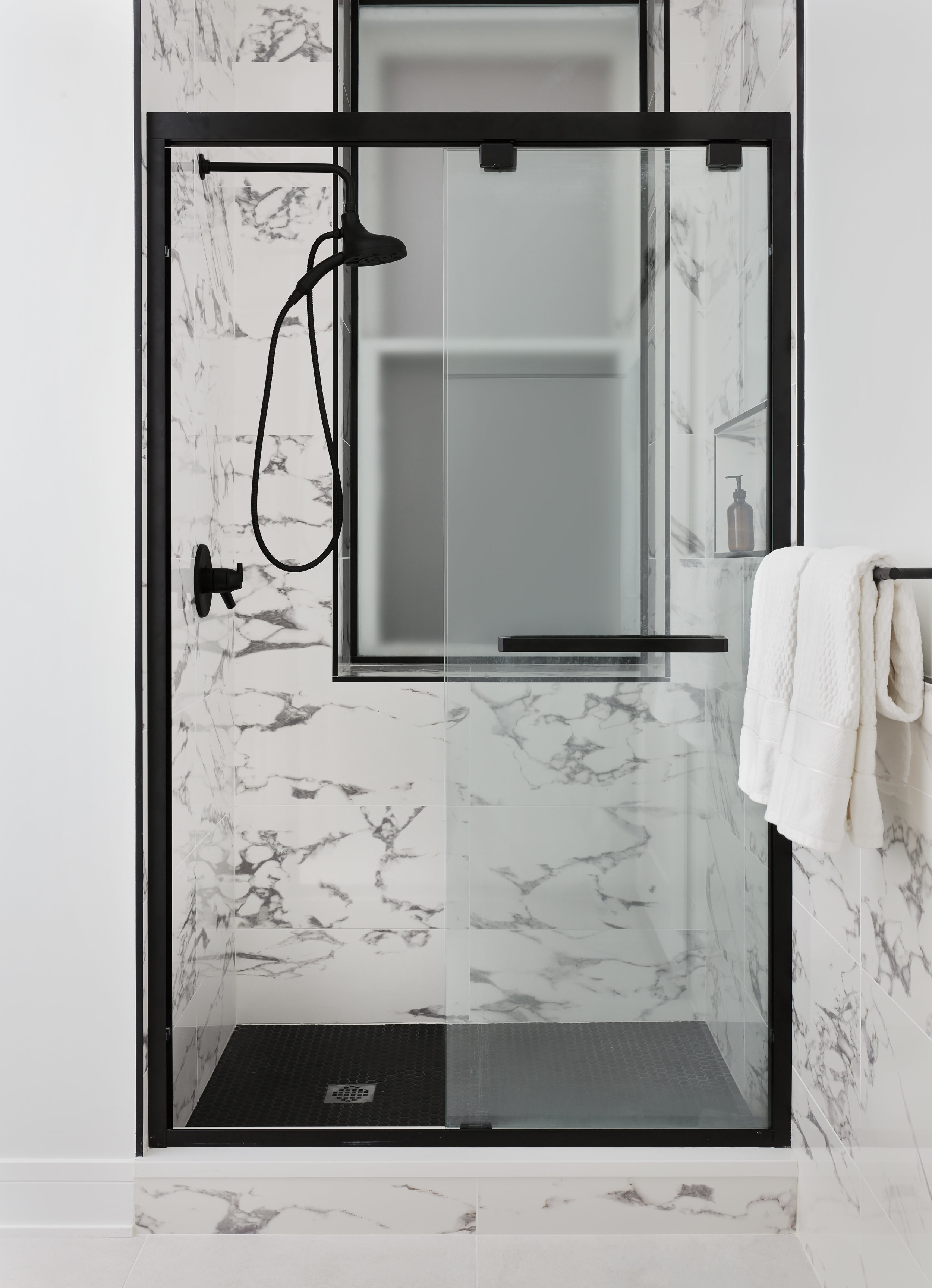 With the new layout of the bathroom, we were able to create a larger walk-in shower where the vanity originally was. We carried in marble-looking porcelain tiles with black metal accents and frosted the window for privacy without blocking natural light.