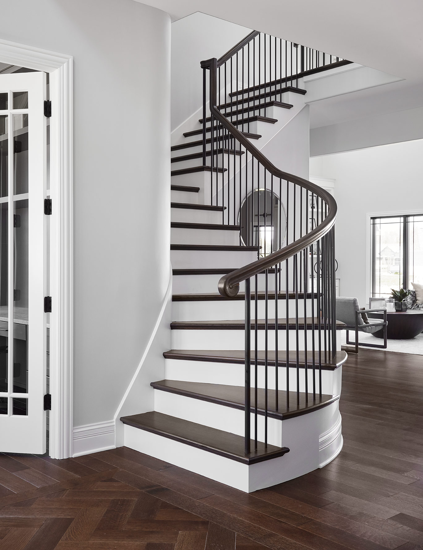 Upon entering the house, guests are greeted with a subtle herringbone texture in the floor and a gran, curving staircase.