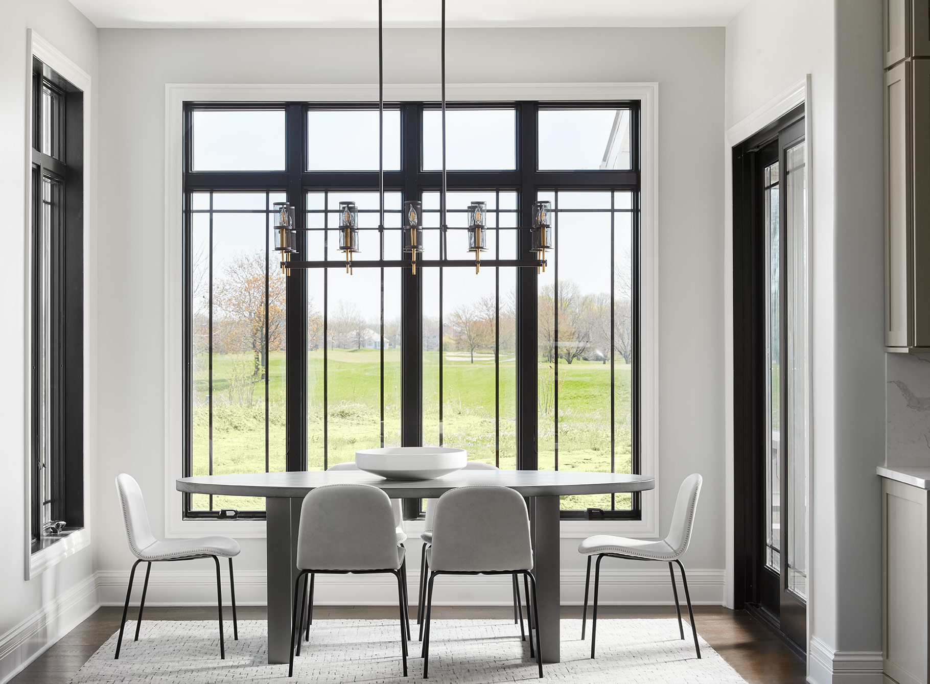 Directly adjacent to the kitchen, the family has a sun-drenched breakfast area overlooking fields and trees behind the house. We kept furnishings simple here to really let the windows and view be the show stopper.