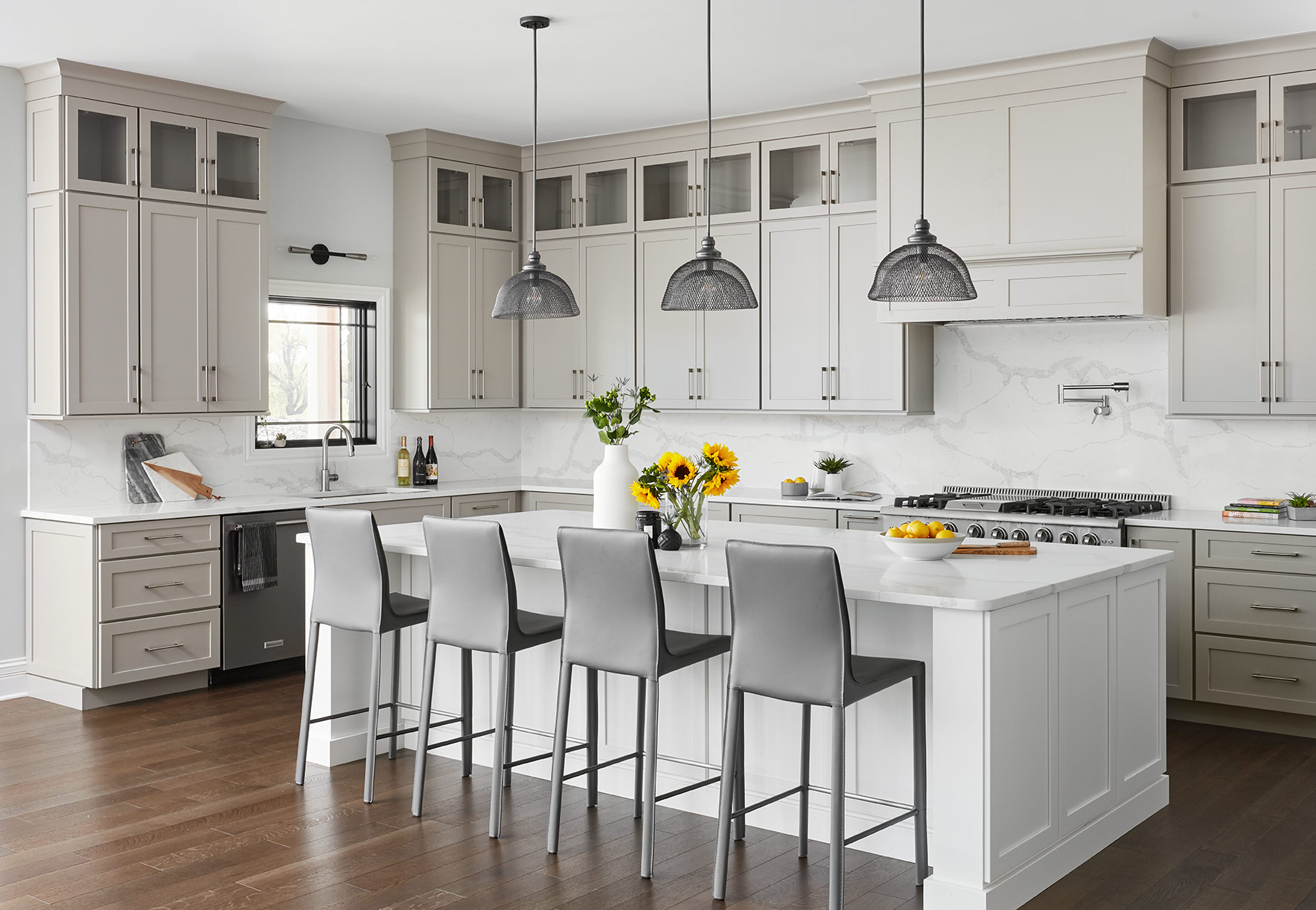 The kitchen was made up of warm gray Shaker style cabinets, carried to the ceiling with glass-door cabinets at the top. The oversized island is a brighter white finish to add some contrast. We carried the marble-looking quartz countertops up the backsplash to add a seamless look and to mitigate any clutter, keeping the design fresh and clean.