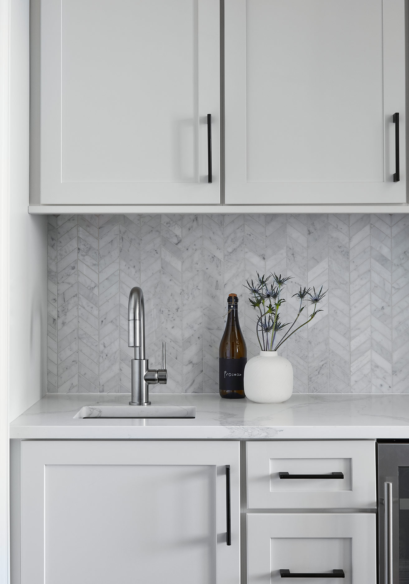 In the Butler's Pantry, we carried in the same white cabinets from the island as well as the same cabinet pulls, but in a matte black to keep things cohesive yet inject some interest in this small area. The herringbone marble backsplash carries in the texture from the kitchen backsplash and counters and ties into the pattern introduced in the entryway floor.