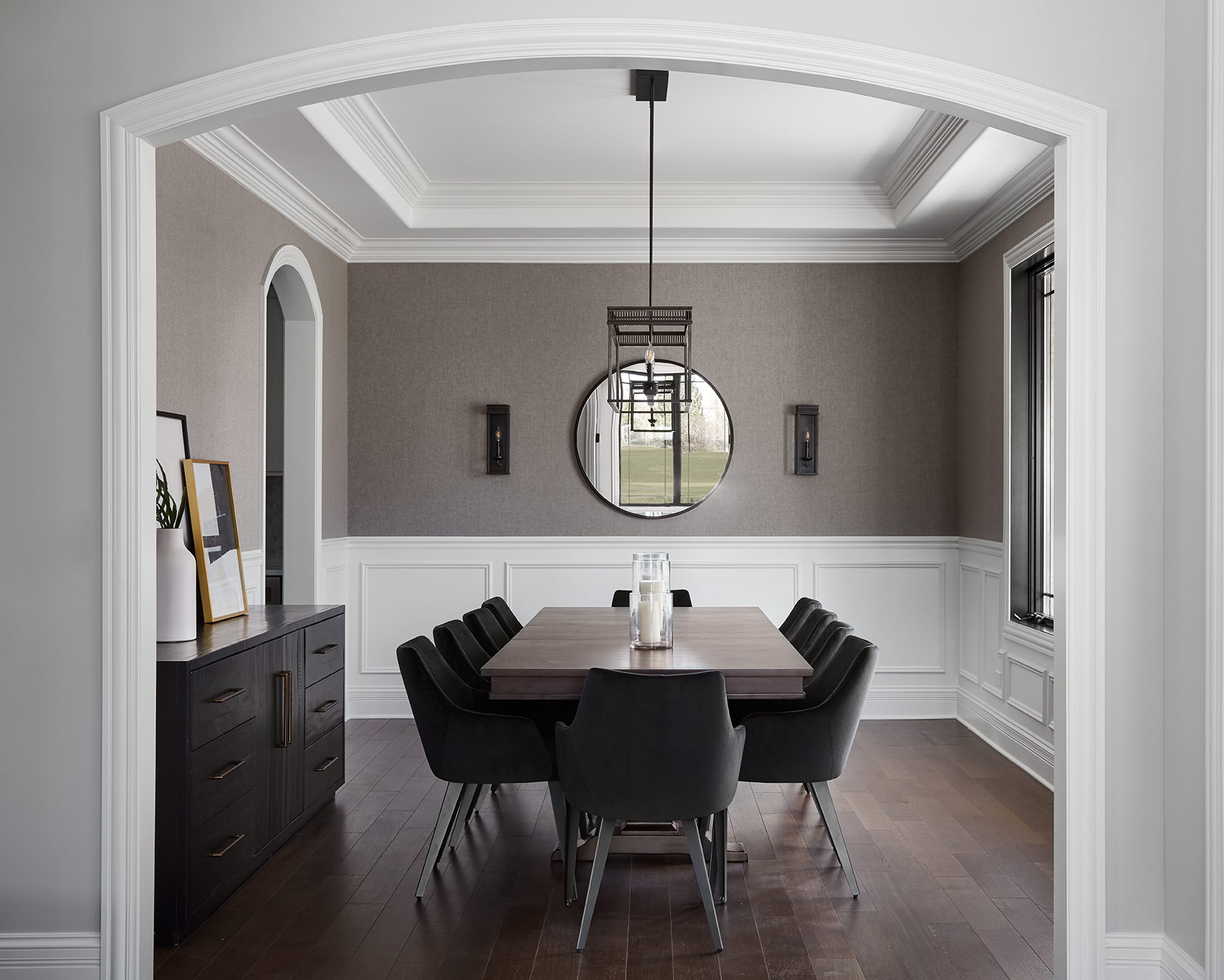 The formal dining room is framed with arched openings and elaborate paneling on the walls and ceiling. We pulled in a textural wallcovering and dark furnishings to add some contrast.