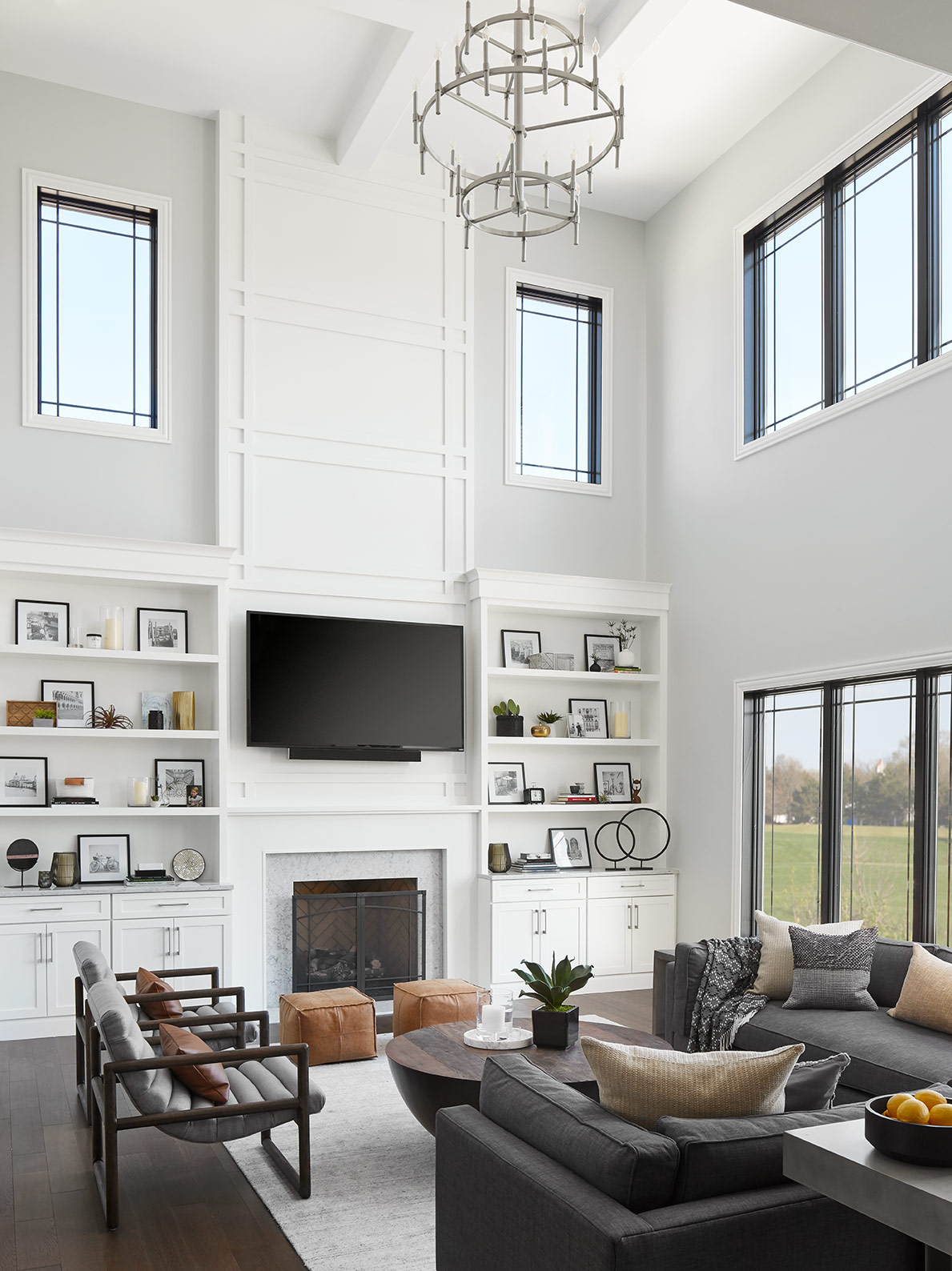 We flanked the fireplace with built-in cabinets and shelving, and carried paneling up the full double-height above the fireplace, mimicking the Prairie-style framing in the windows. The furniture creates a sophisticated area for entertaining while providing a comfortable place for the family to relax in.
