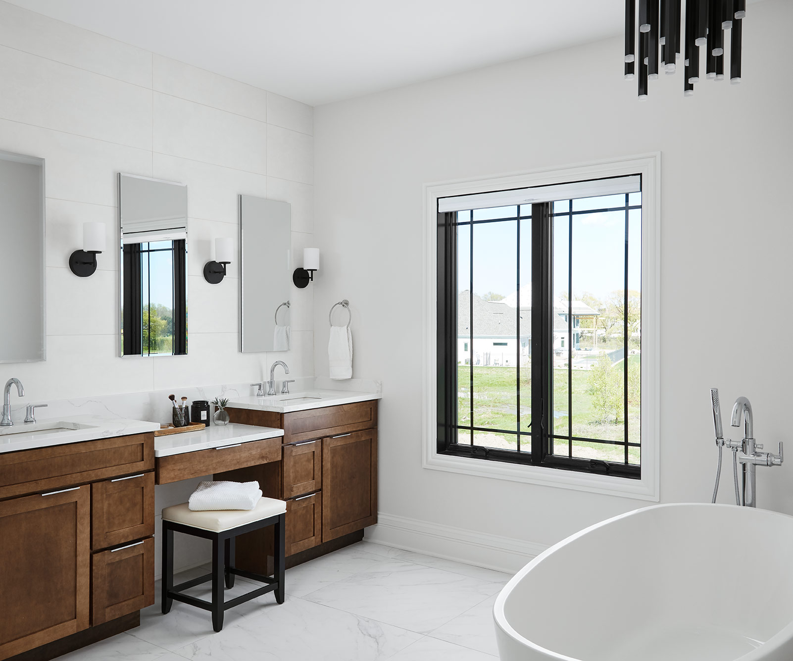 The master bath continues a serene palette with marble floors and a textured white tile behind a rich, walnut vanity. A freestanding tub provides a luxurious escape and the dripping chandelier above it pulls in some drama and elegance.