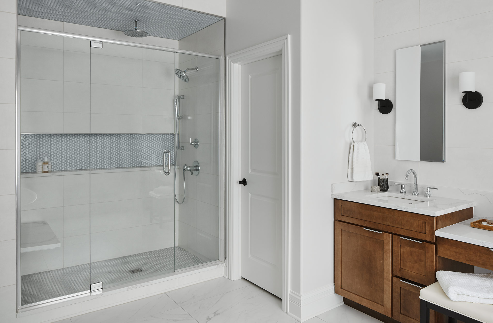The shower provides a spa-like retreat with it's overhead rainhead and adjustable hand-held. A long shampoo niche pulls in a subtle, geometric pattern, carried through to the floor and ceiling.