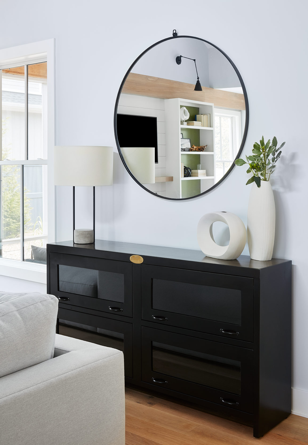A black metal credenza and oversized mirror provide additional storage and add some contrast to the room.