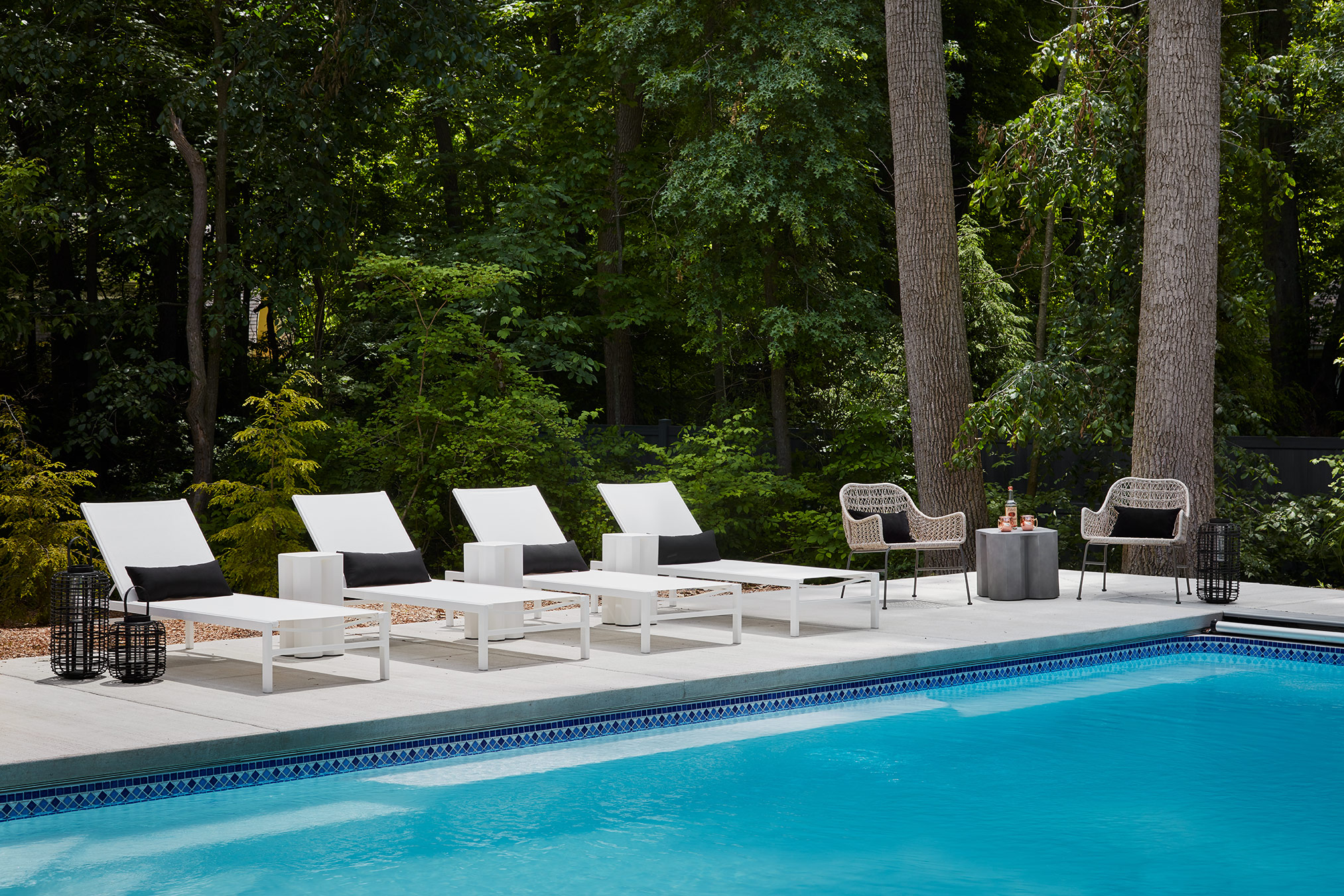 Beside the stunning pool, we introduced crisp white chaise lounges and textural woven lounge chairs. We completed the look with black accent pillows, concrete side tables and black lattice lanterns.
