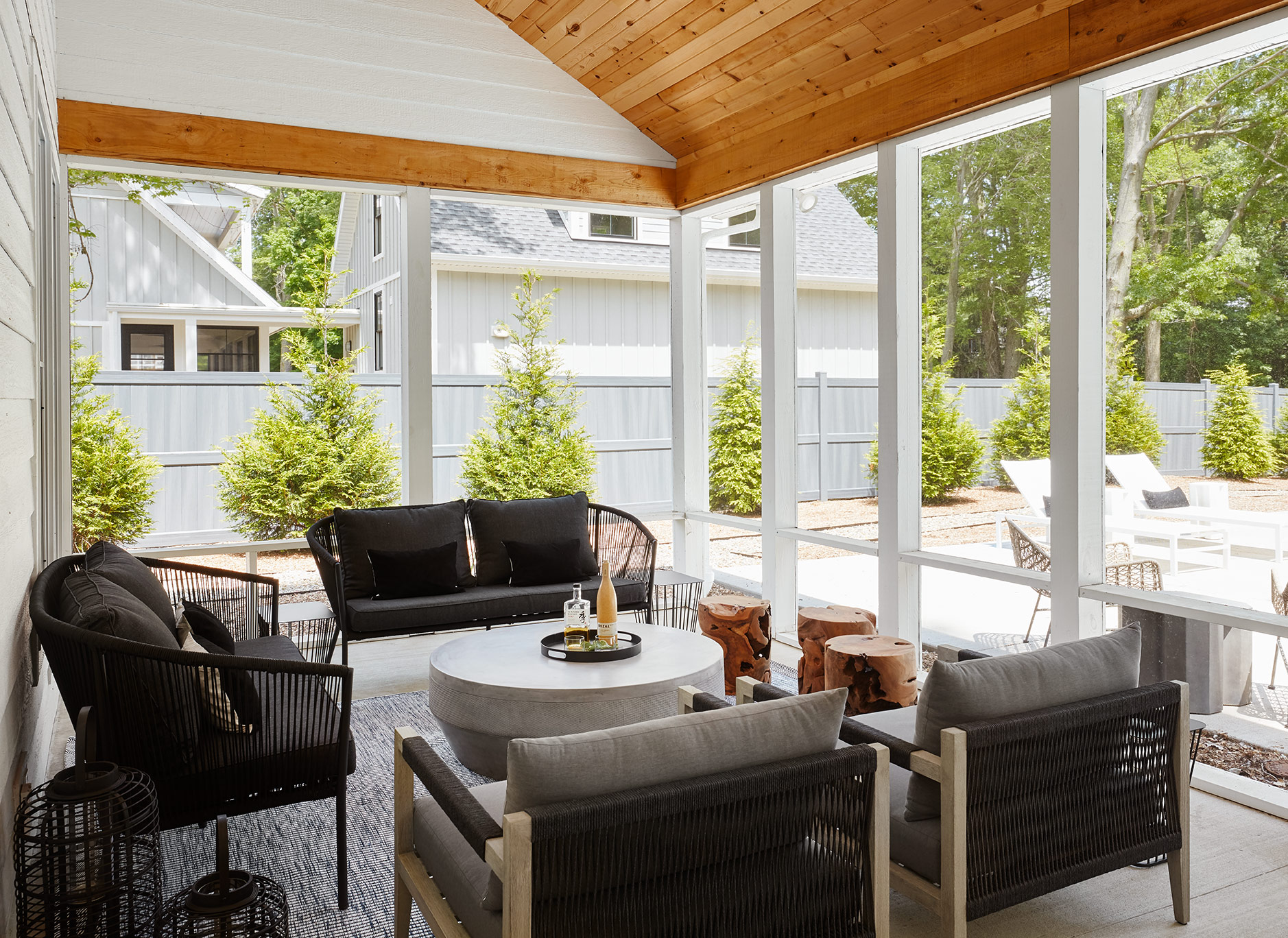 Before we reveal the bedrooms, we need to step outside to the incredible screened in porch. The name of the game out here was texture! We incorporated natural materials with a concrete coffee table and raw teak stools and contrasted those tones with black woven accents.