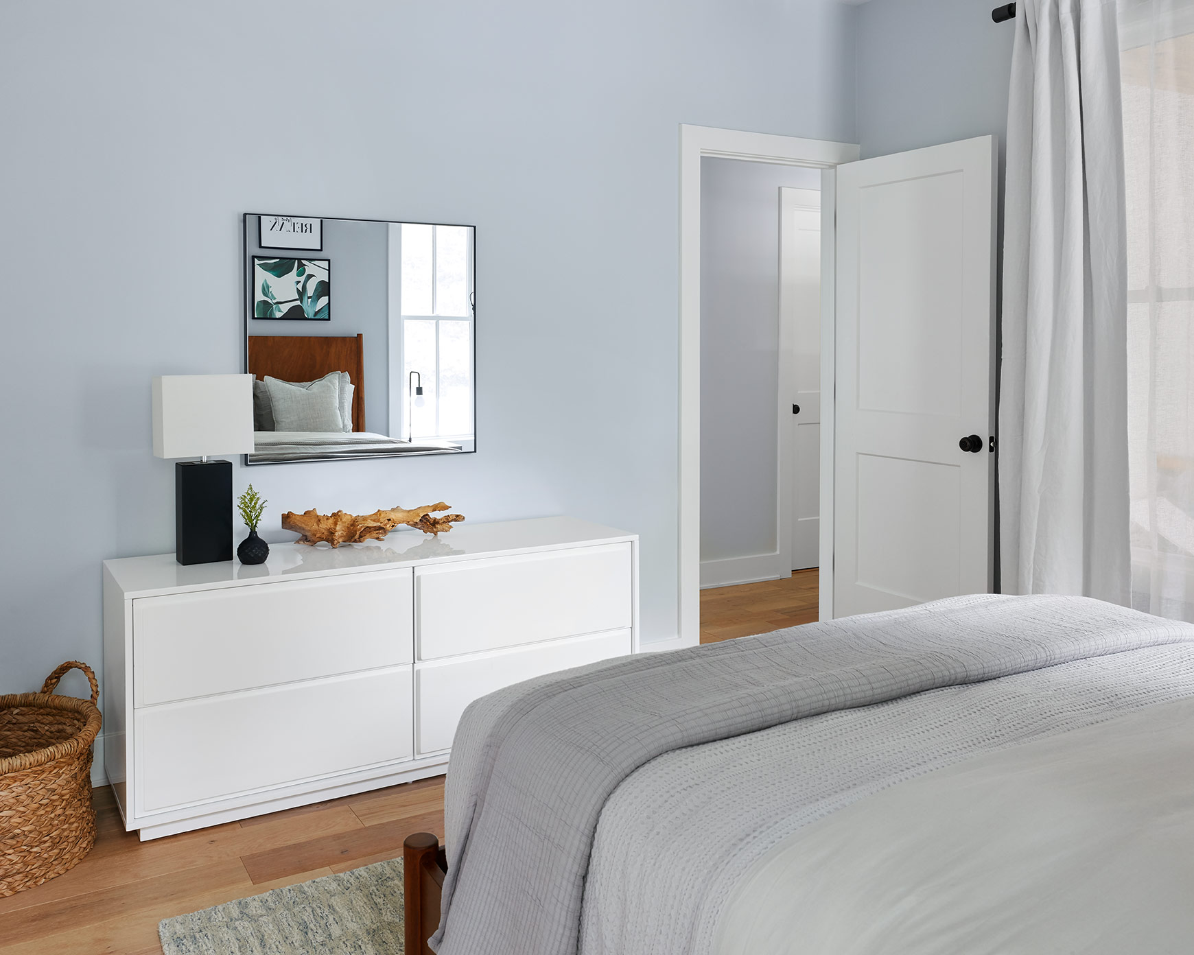 Opposite the bed, a crisp white lacquer dresser completes the room with natural textures to add contrast and interest.