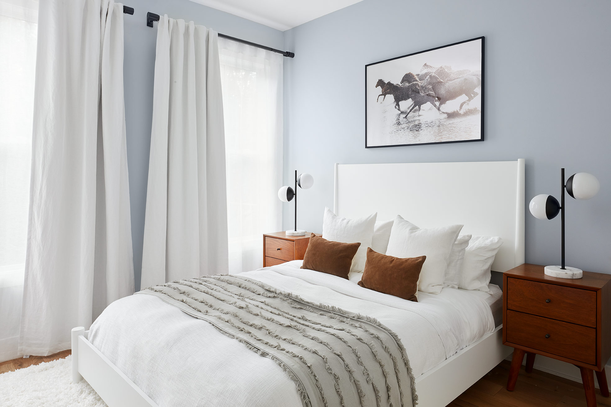 The second bedroom has the same headboard as the first but in white, to keep the spaces cohesive. Warm wood nightstands and brown suede pillows add contrast to the crisp white bedding and plush white rug.