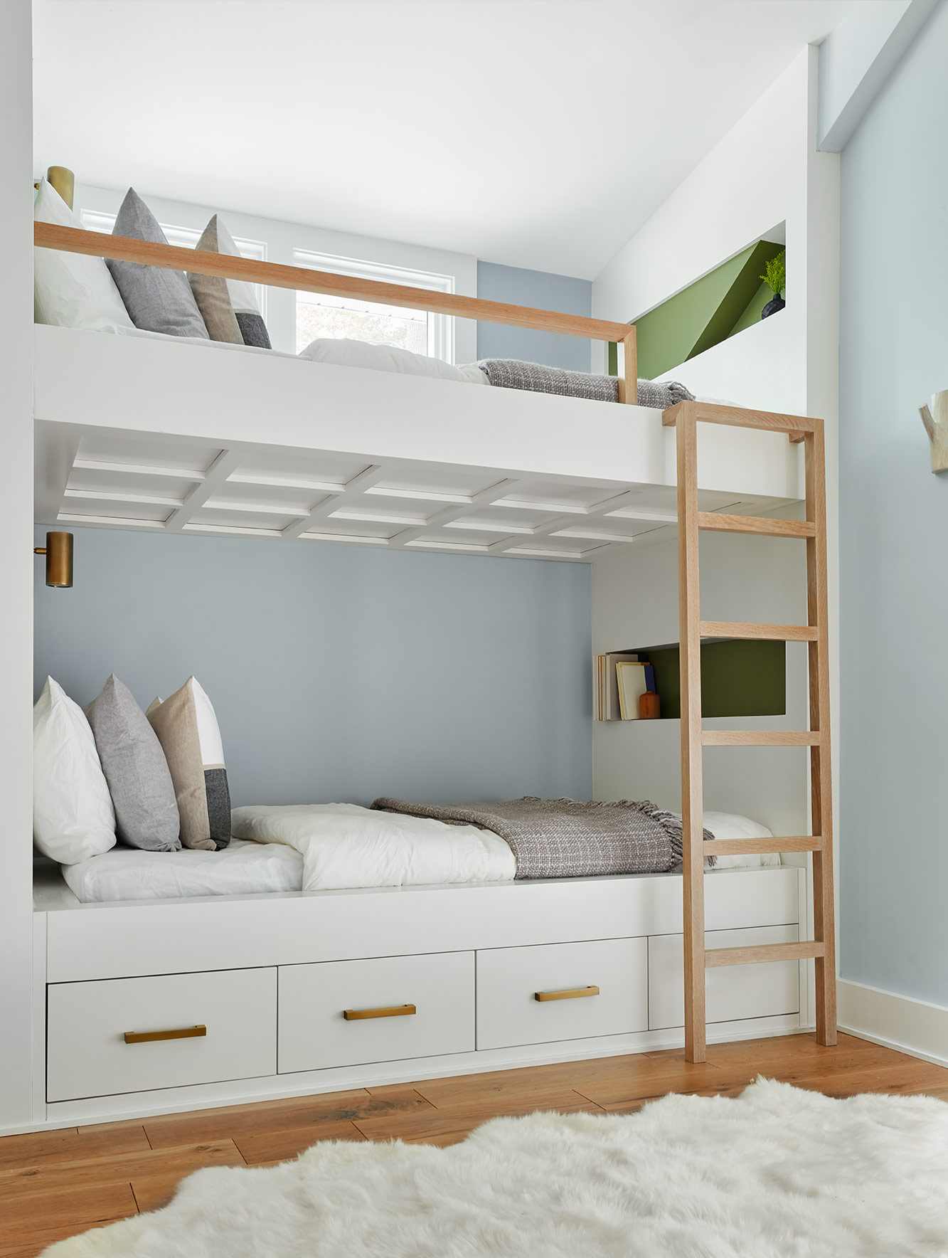 Soft-close drawers beneath the bed provide integrated storage and niches at the head and foot allow the users to keep books or water nearby. We tucked modern brass sconces at the head for reading to really complete the cozy, inviting space.