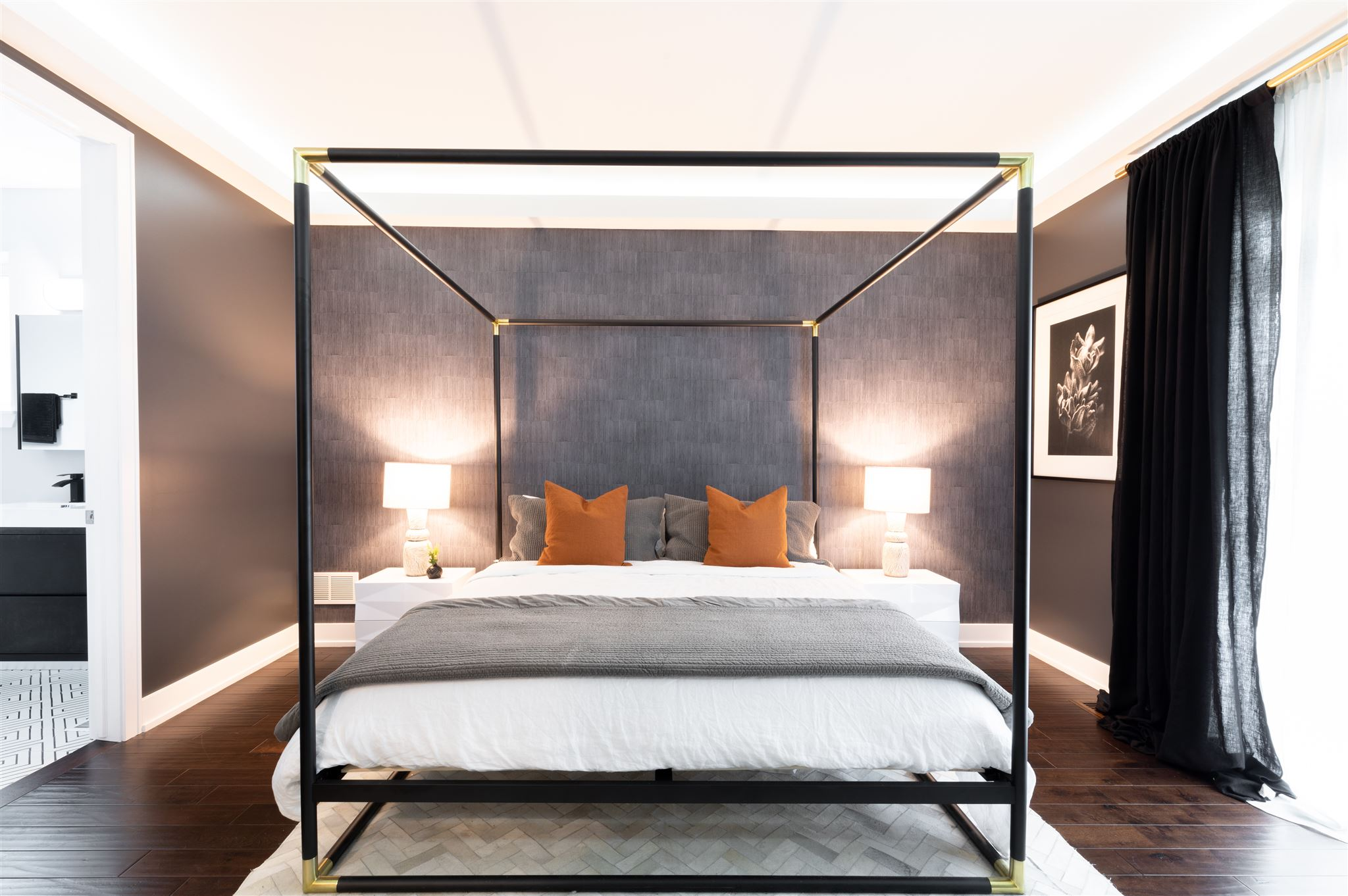 The master bedroom got a moody update as well with dark gray walls and a textured wallpaper behind the new canopy bed. Black and brass metals add a sharp contrast to the otherwise soft palette.