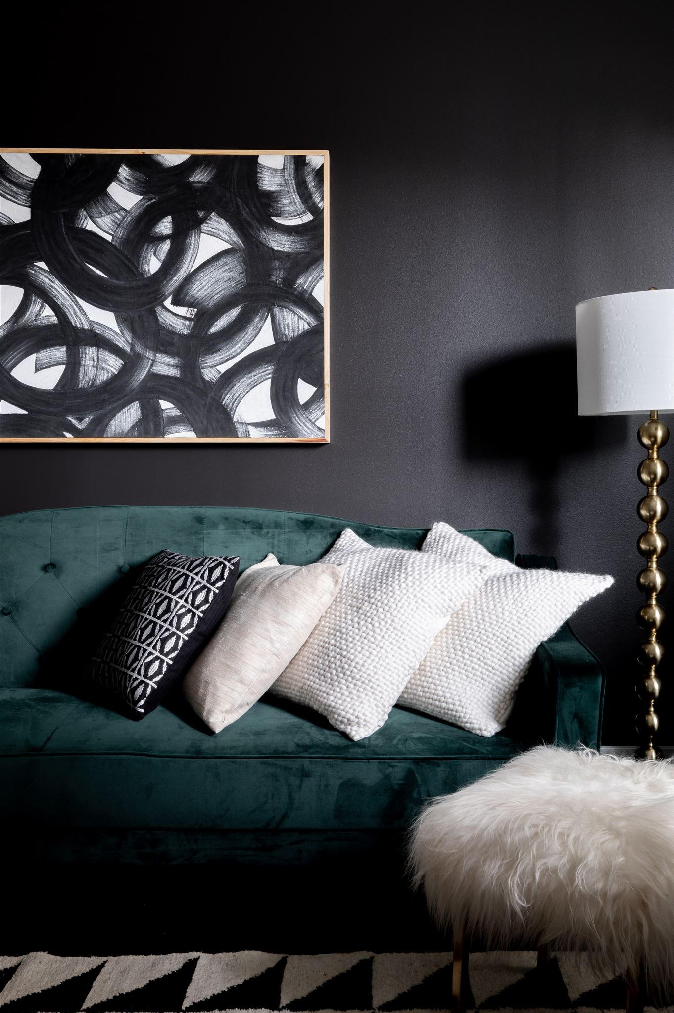 In the office, we carried in one last black wall with a luxe, green velvet sofa in front of it. The rug in here pulls in a black and white geometric pattern to create a cohesive feel with the rest of the house.