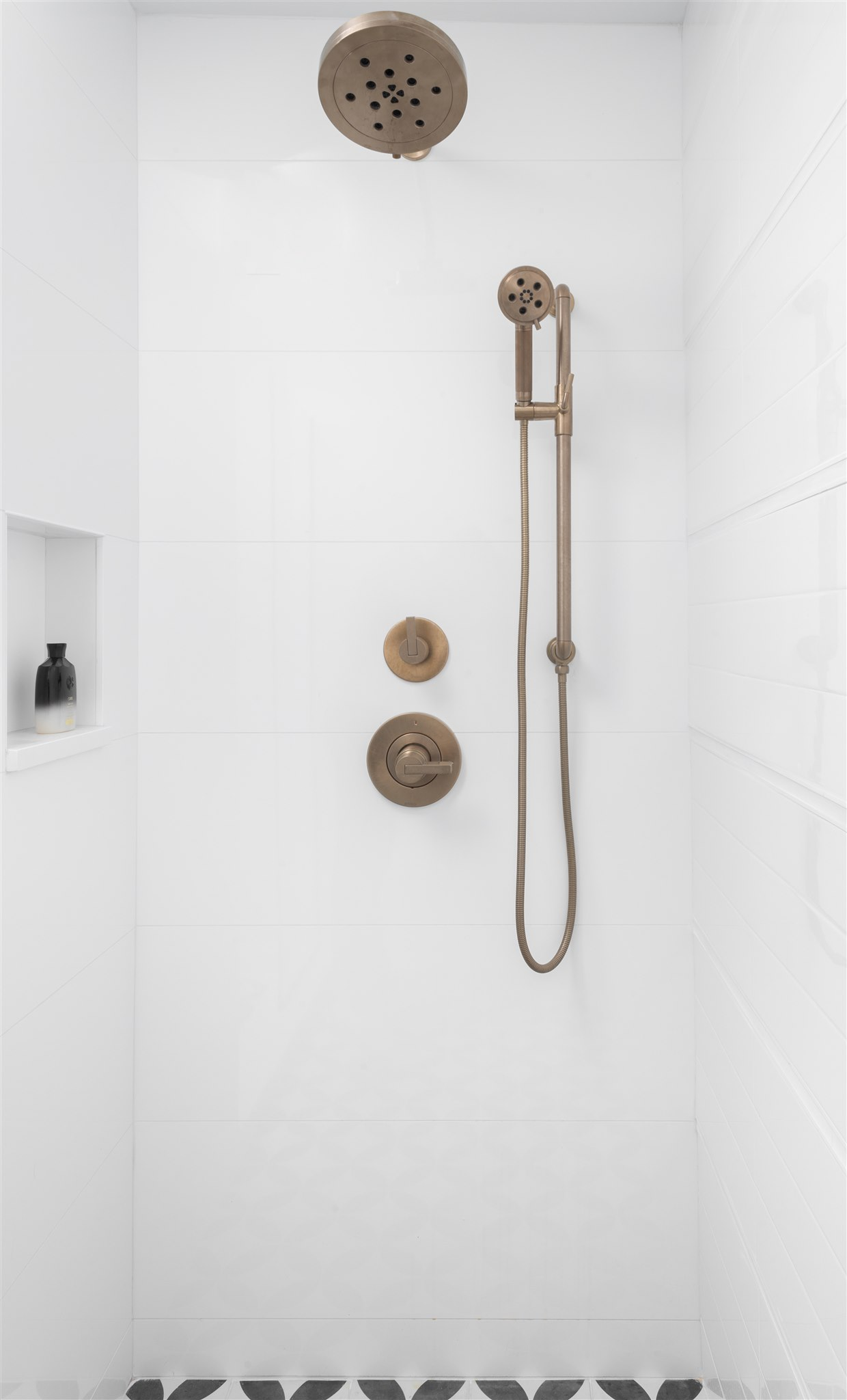In the shower, we carried in large format white tiles towards the front and back and then played with the pattern of the long subway tiles on the side wall so that all of the horizontal grout lines aligned with the larger format tiles.