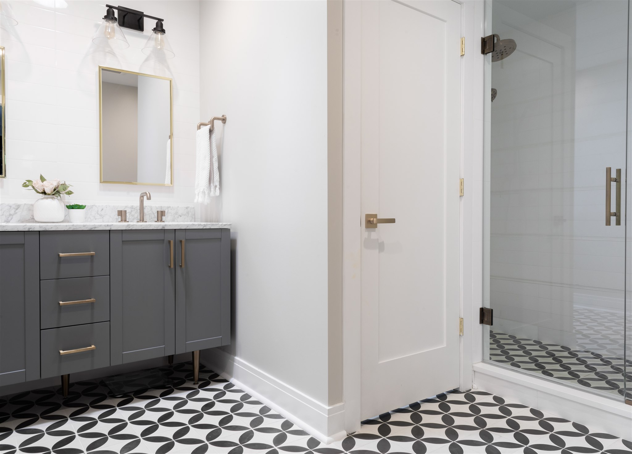 We pulled in some fun, cheerful patterns in this space to add contrast to the otherwise light and soft bathroom. The gray and marble vanity gets warmed up with brass accents, which we carried throughout the rest of the bathroom in plumbing fixtures and door hardware.