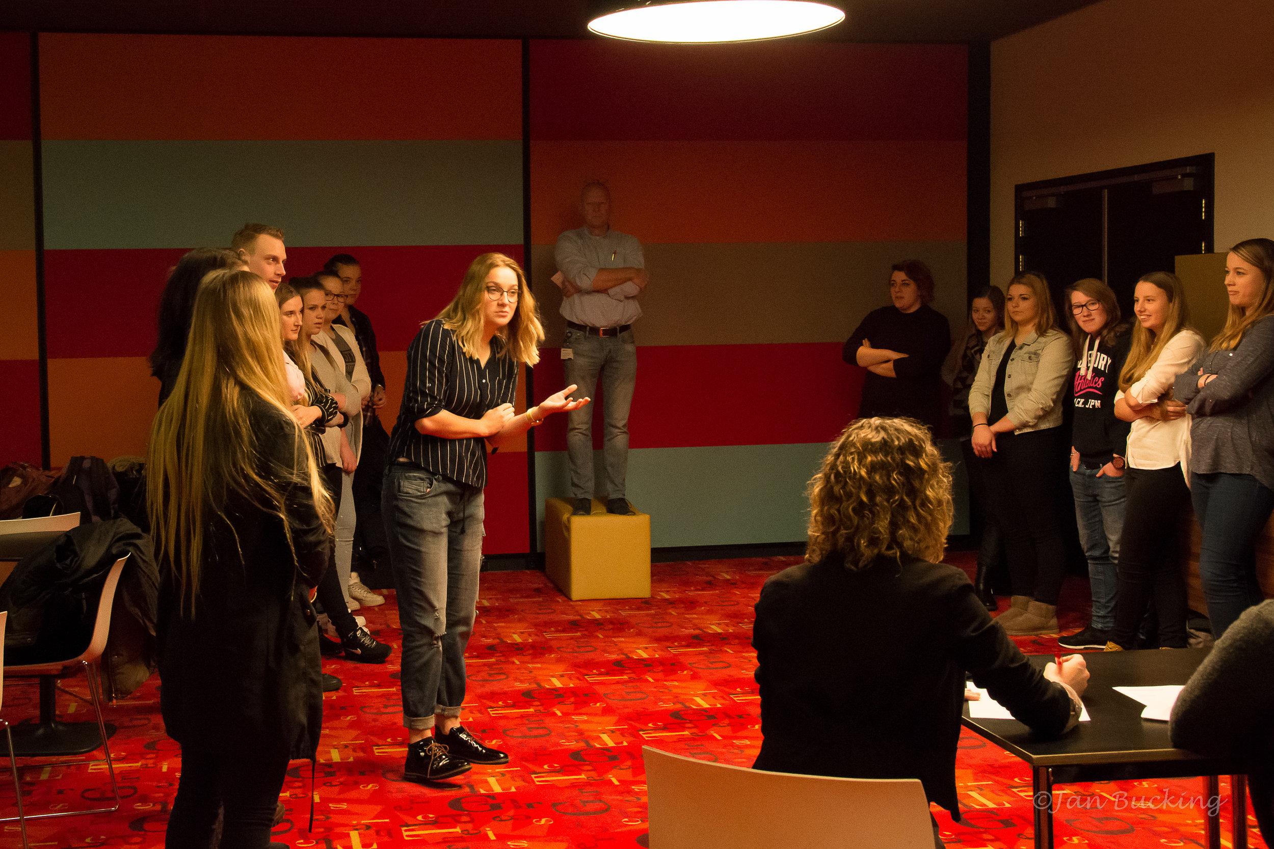 Studenten in debat. Docenten werken samen in duo's bij het leiden en jureren van de debatten.