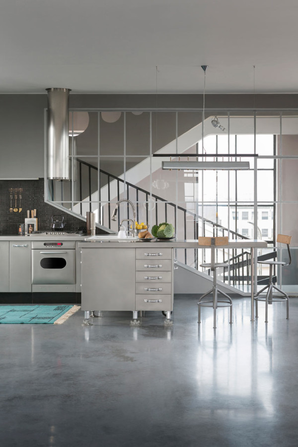 The renovated kitchen is done primarily is stainless steel and suits the industrial feel of the space without going overboard. Another area rug is used to add texture, color and softness underfoot in a work area.