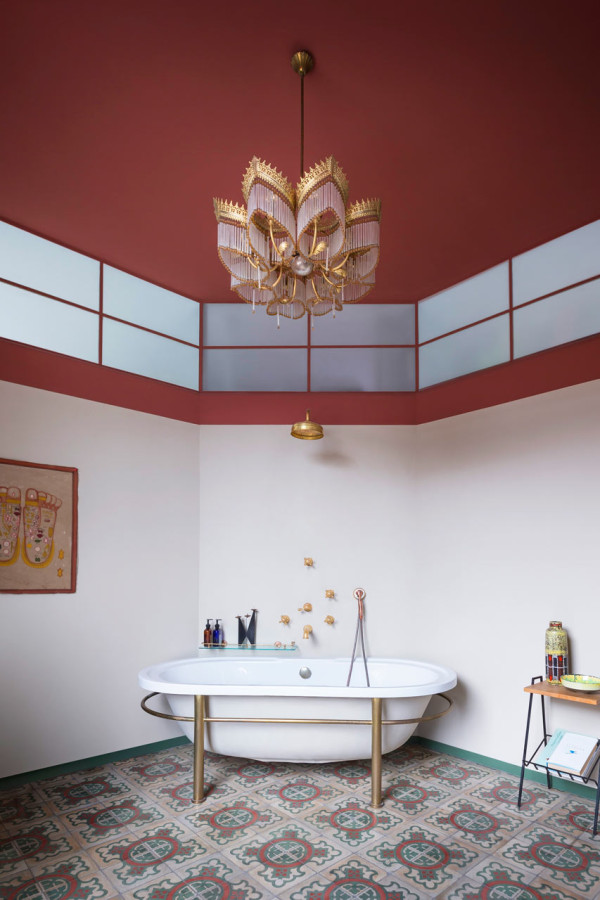 The bold light fixture and unique bathtub add to this unique bathroom space.
