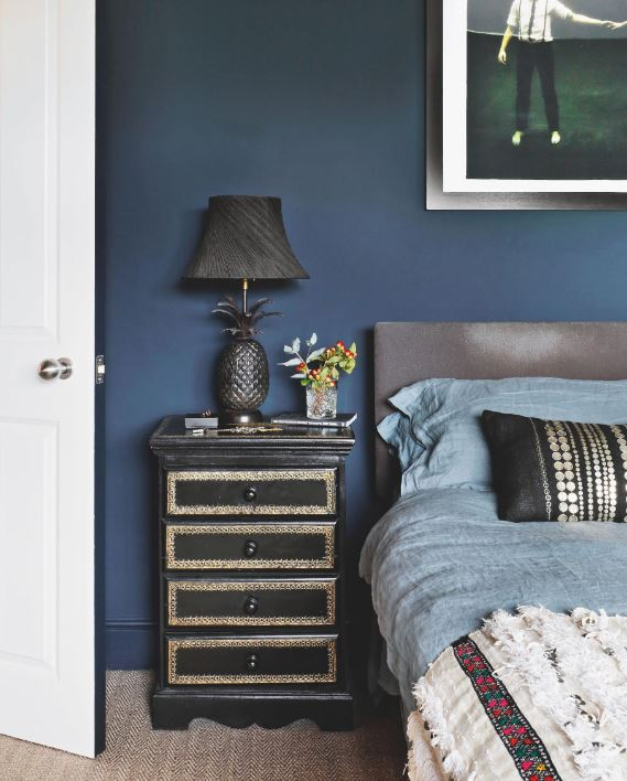 The dark tones are repeated in the bedroom, offering a cozy feel that is brightened by touches of warm metals.
