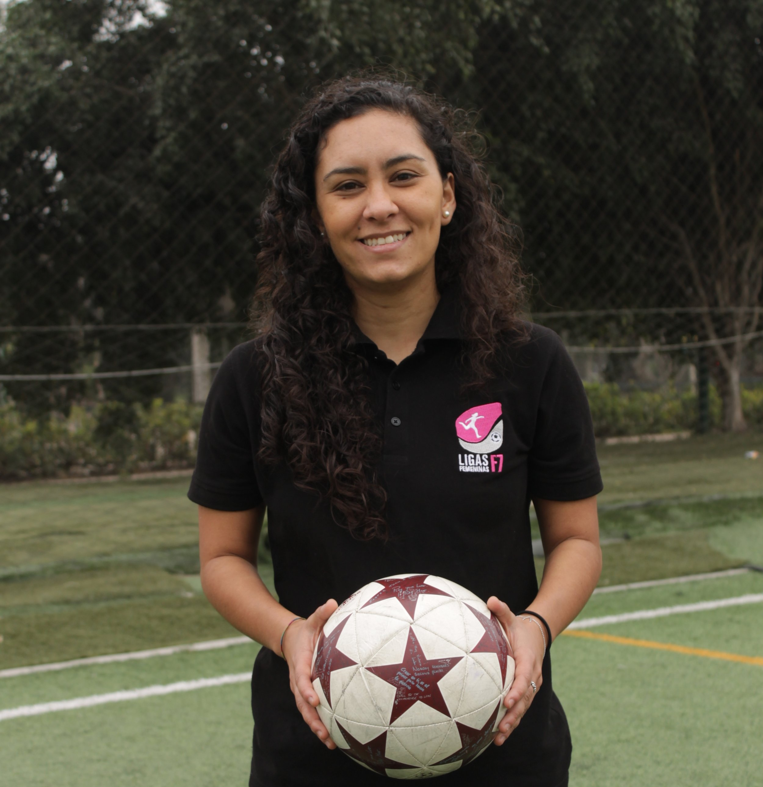 Image description: Thalia standing with soccer ball in her hands on a soccer field dressed in polo with the Ligas Femeninas de Futbol logo.