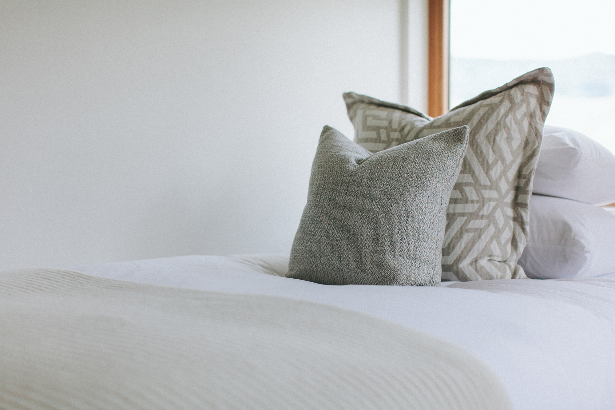 A modern white bed with two gray pillows