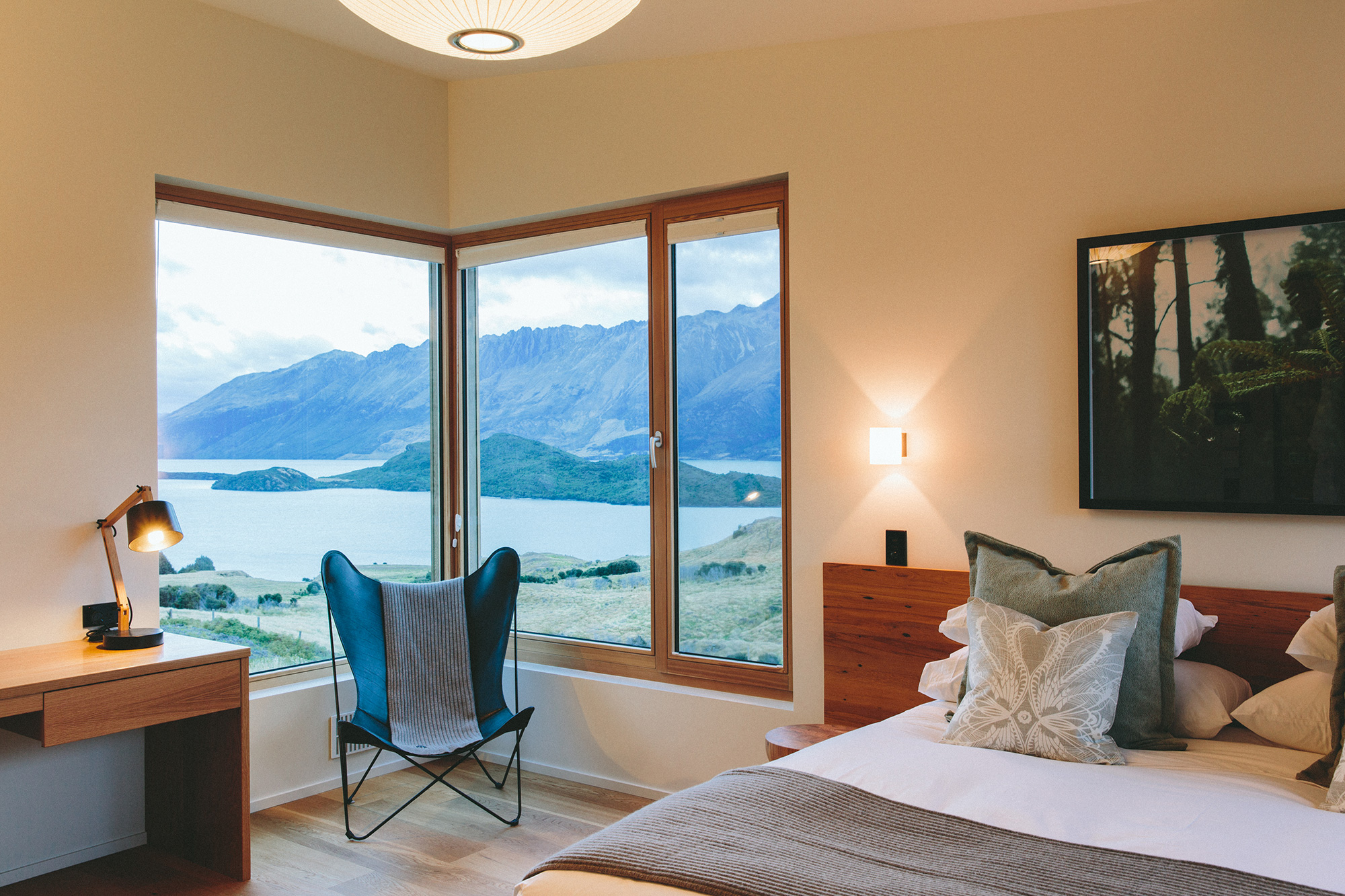 A bedroom setting with big windows looking out at a mountain view