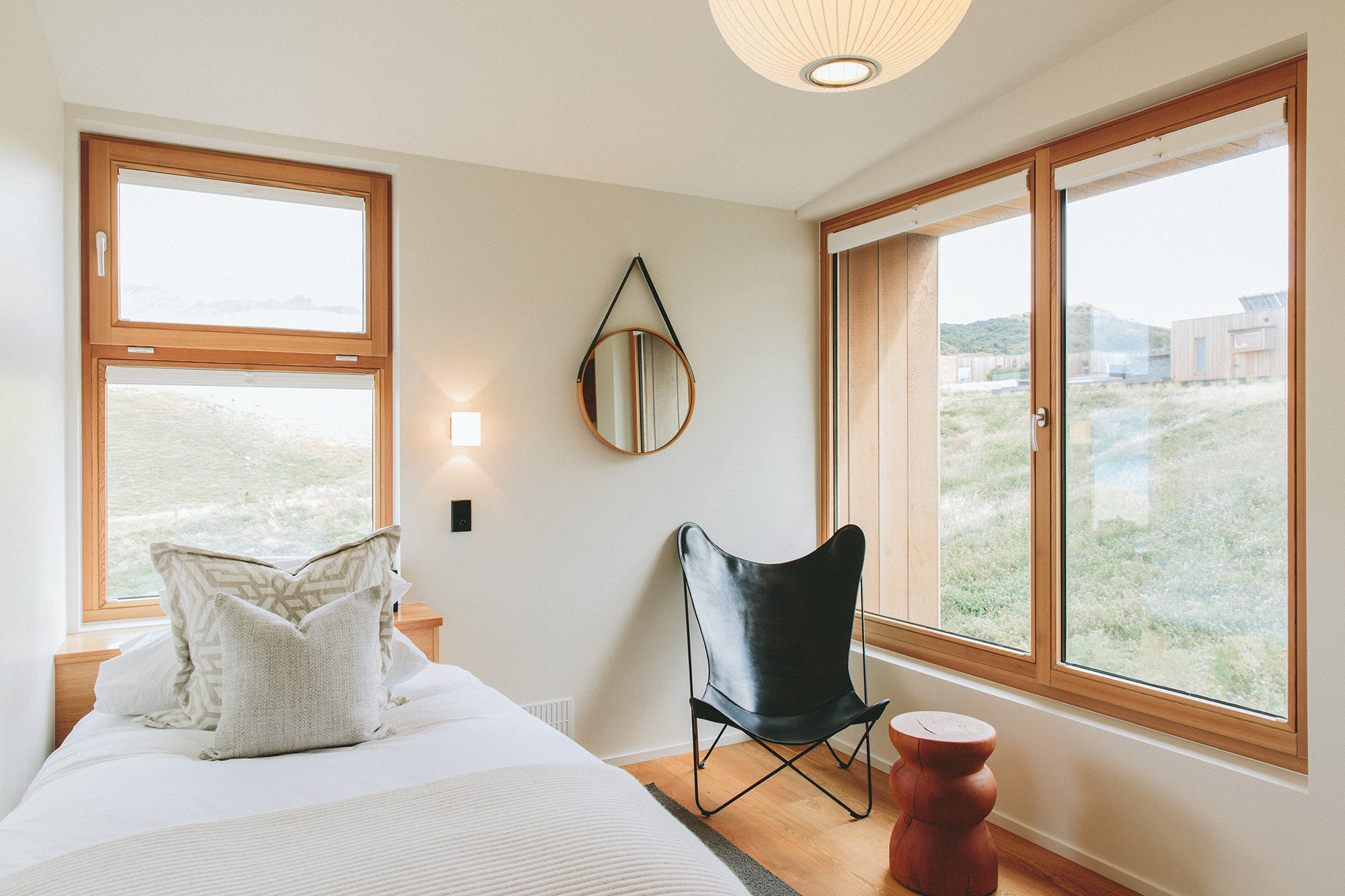 White bed with two gray pillows an windows looking out at a mountain view.