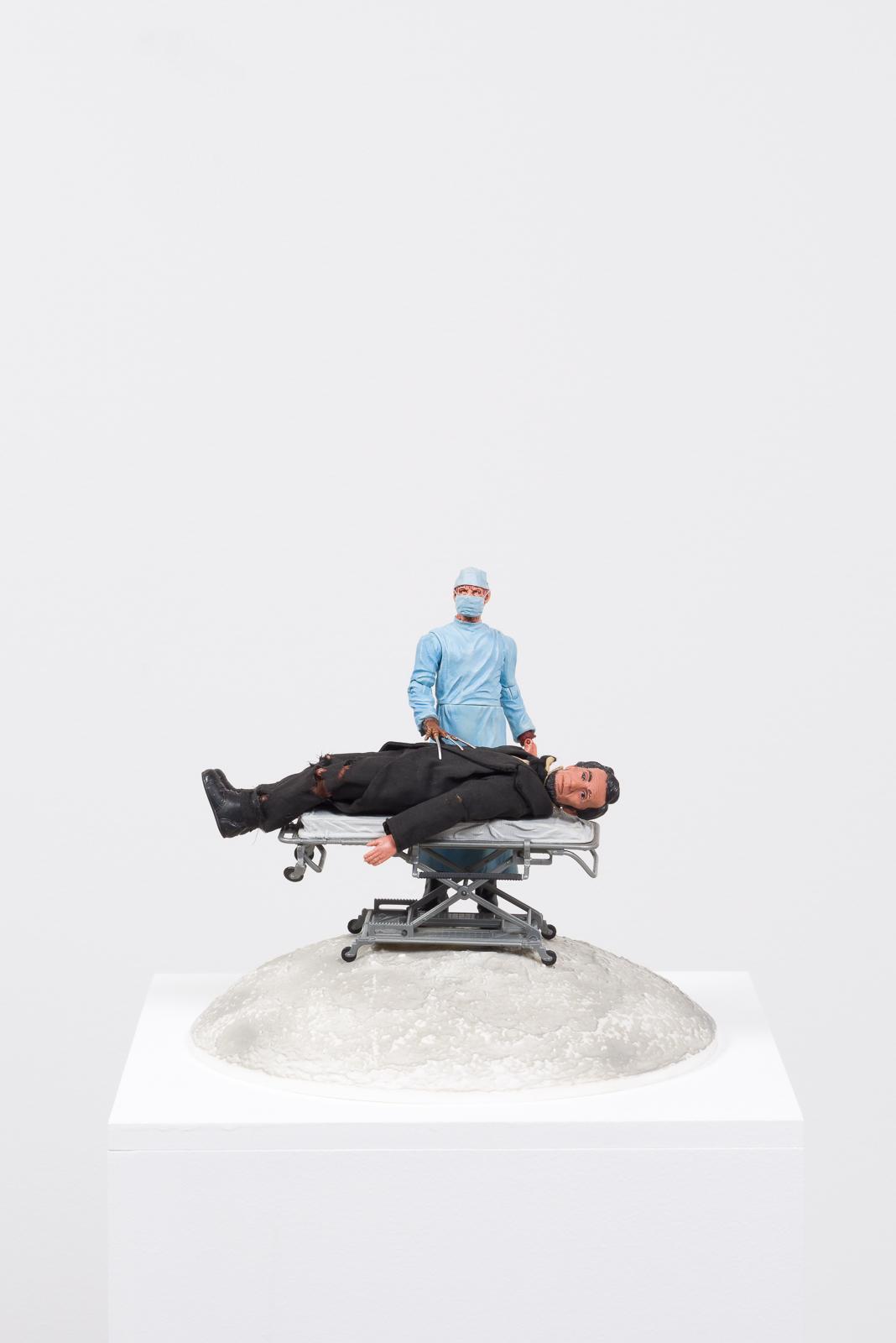 Healthcare Cuts, 2017  Plastic moon model, plastic hospital gurney, plastic and vinyl action figures, pedestal