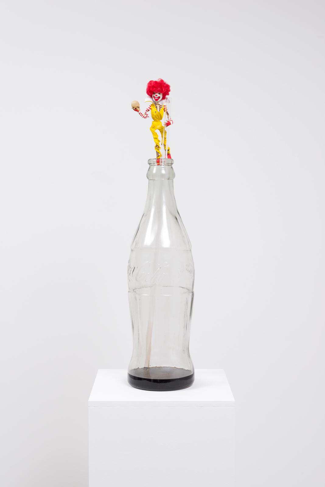 The Last Mexican Coke, 2017  Jumbo glass Coke bottle, Plexiglas, resin and vinyl action figure, pedestal