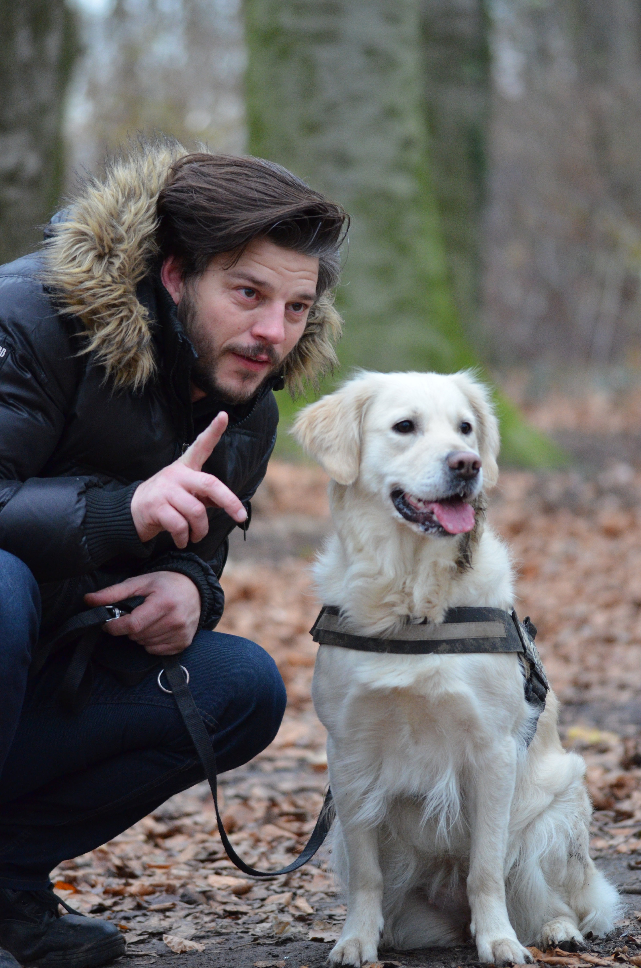 Canva - Man Wearing Black and Brown Fur Hoodie Jacket and Blue Pants Holding Dog Leash Beside White Short Coat Dog (1).jpg