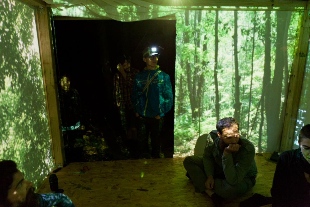 "Terri Chiao and Adam Frezza used footage taken during daytime meditations in and around the pavilion to project onto the walls of the structure at night. The footage draws attention to natural sunlight ""projections"" through the forest canopy."